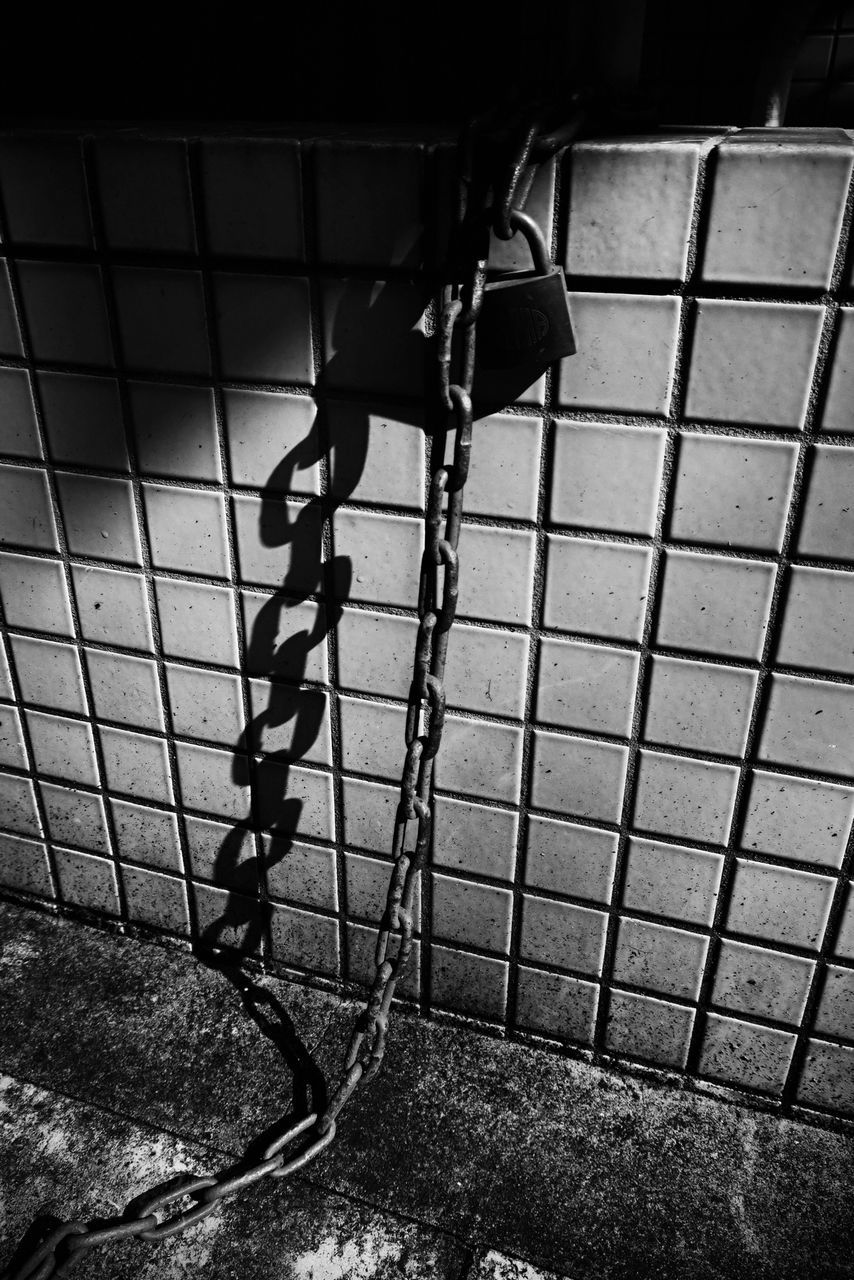 Metallic Chain Attached To Padlock Against Wall At Night