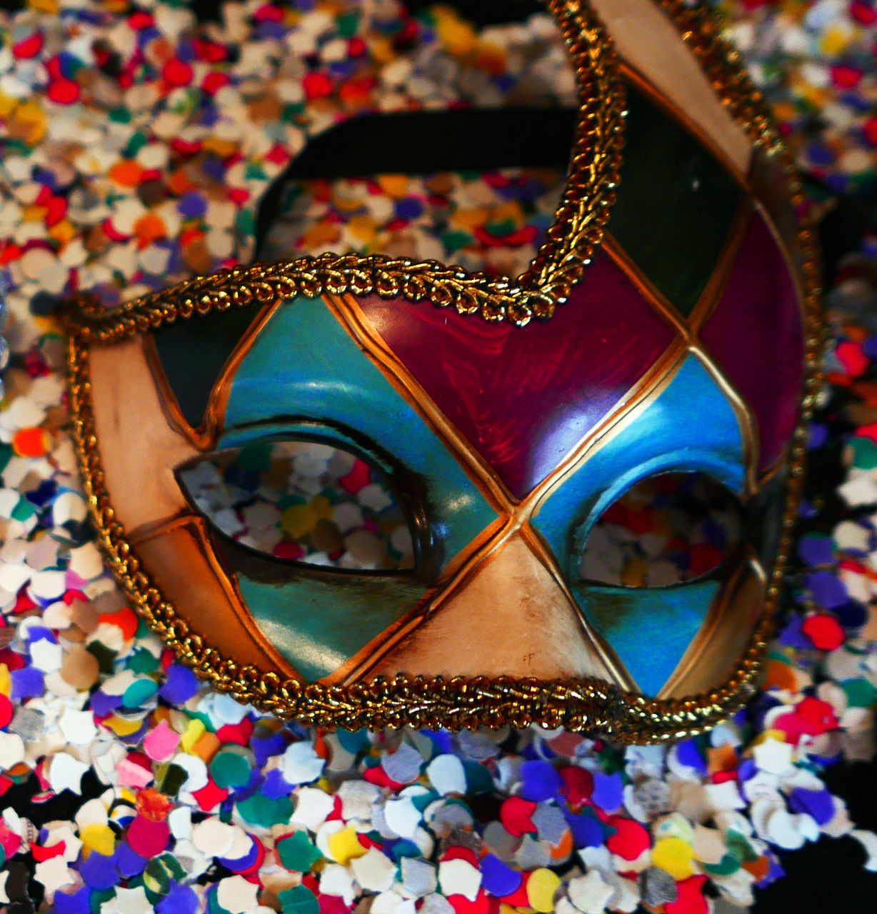 High Angle View Of Venetian Mask On Confetti At Table