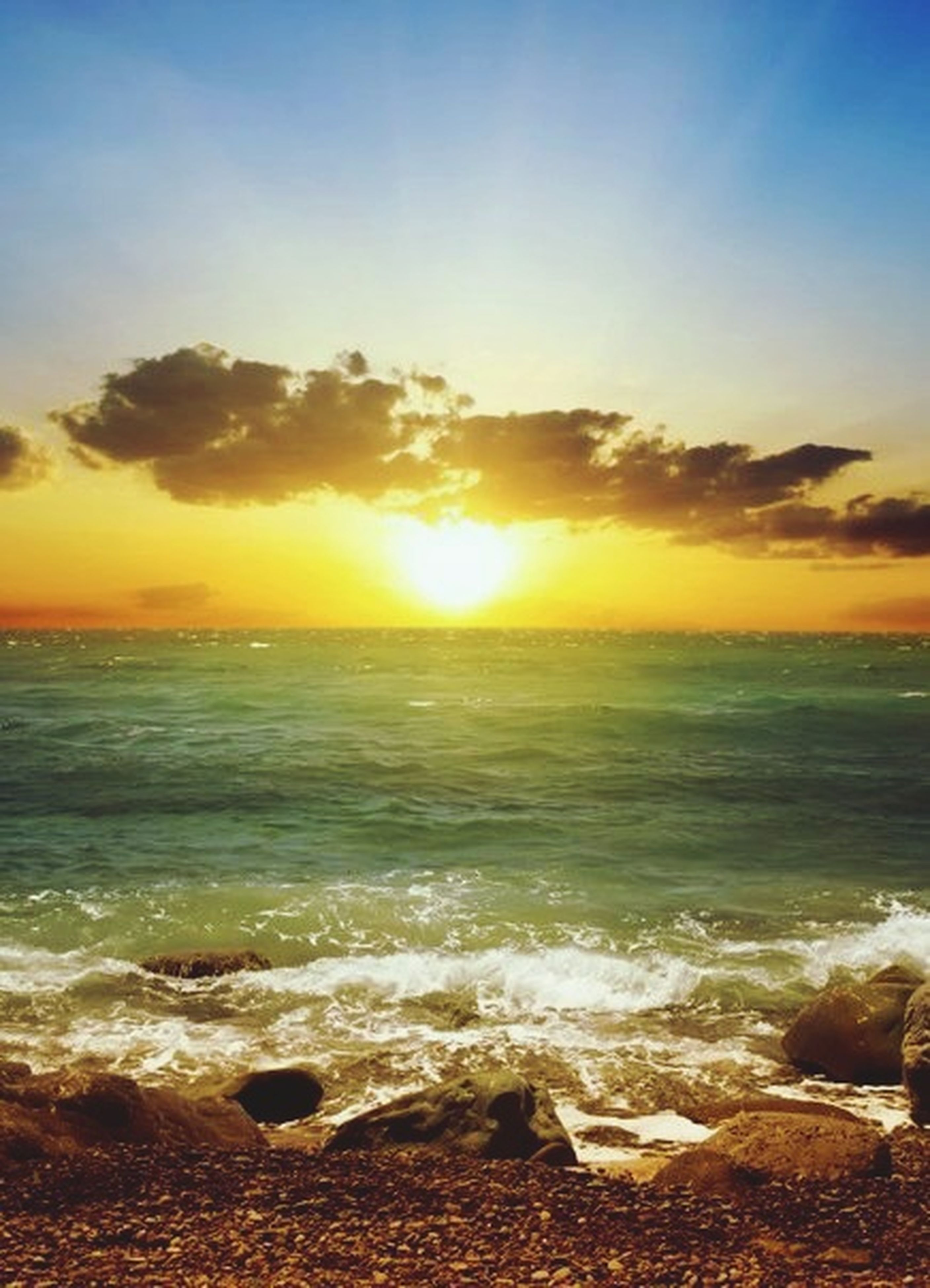sea, water, horizon over water, sunset, beach, scenics, beauty in nature, sky, shore, tranquil scene, wave, tranquility, orange color, nature, idyllic, sun, surf, cloud - sky, rock - object, sunlight