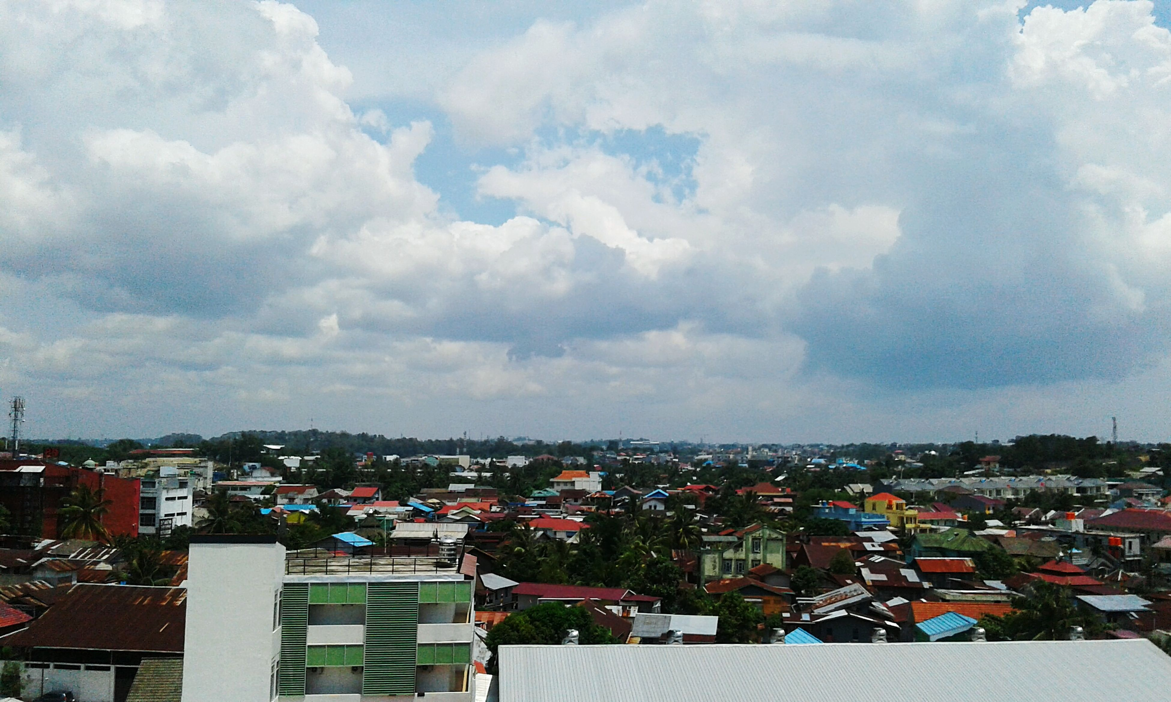 building exterior, architecture, built structure, cityscape, city, sky, crowded, cloud - sky, residential district, residential building, residential structure, cloudy, high angle view, cloud, house, community, human settlement, outdoors, city life, town