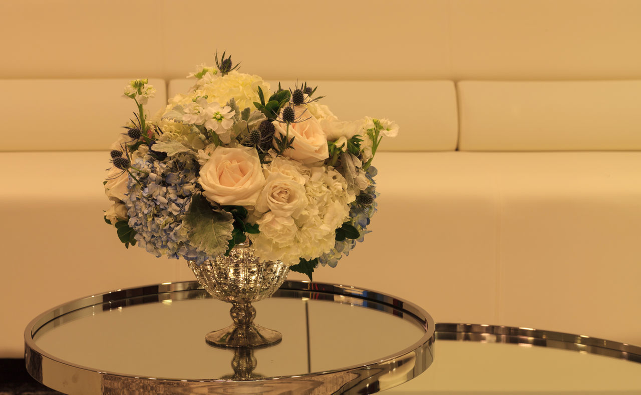 Wedding bouquet in a silver vase on a mirror table with white chairs and a sofa in the background. Flowers include white poppy Papaver species, white roses, blue thistle flowers, hydrangea and sweat pea. Blue Bouquet Eryngium Flower Arangement Flowers Glamorous  Hydrangea Luxury Mirror Table Pink Purple Rosa Roses Silver Vase Sweet Pea Flower Thistle Flower Valentine's Day  Wedding Wedding Day White