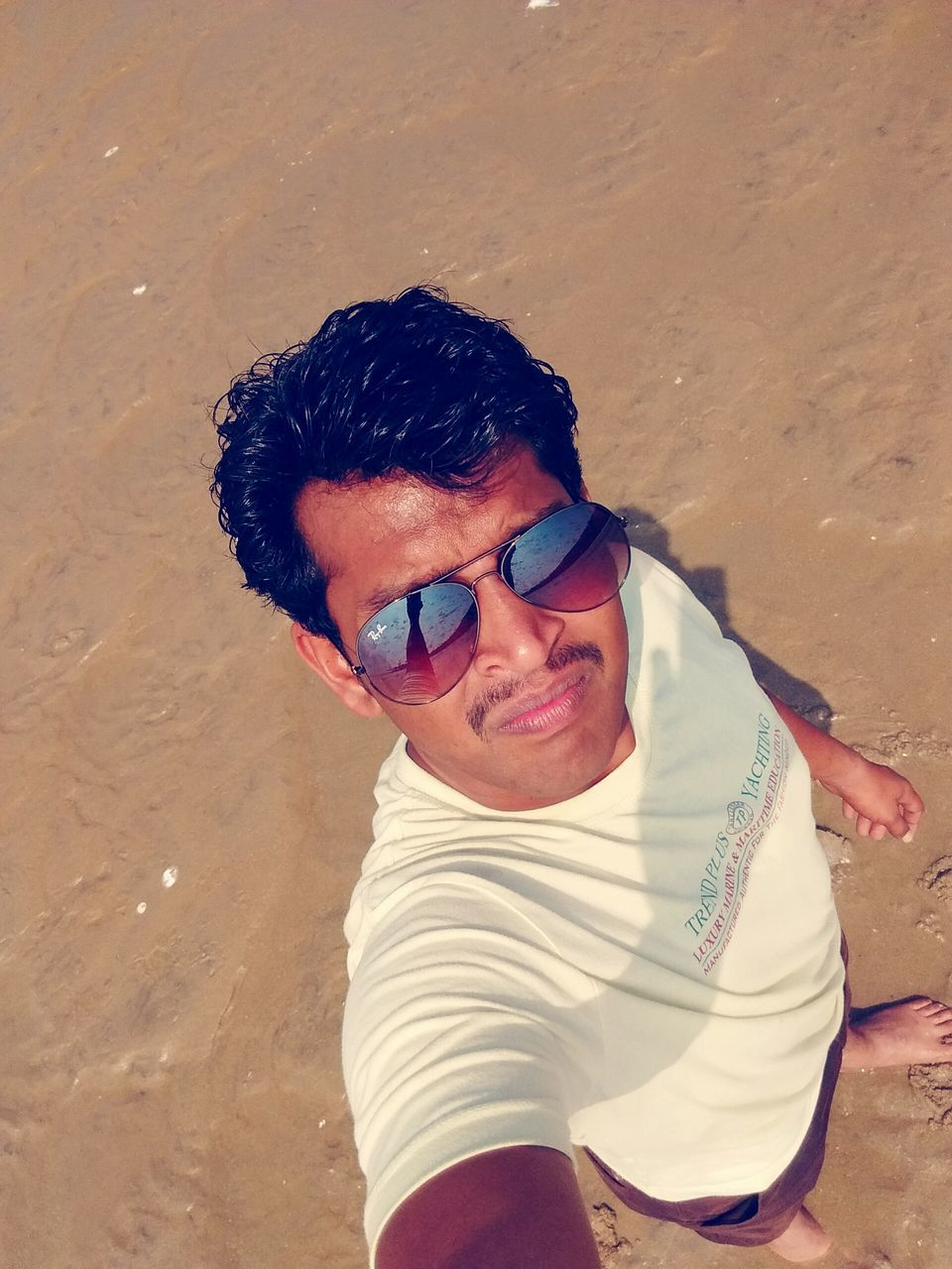 real people, sand, one person, beach, happiness, leisure activity, smiling, looking at camera, portrait, lifestyles, front view, high angle view, casual clothing, outdoors, day, young adult, childhood, eyeglasses, nature