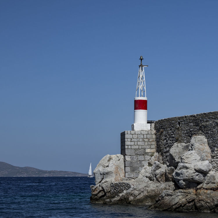 Ýdra Architecture Astrology Sign Blue Business Finance And Industry Clear Sky Day Flag Greece Hollidays Island Lighthouse Mediterranean Sea Nature No People Outdoors Scenics Sea Sky Water Ýdra, Greece