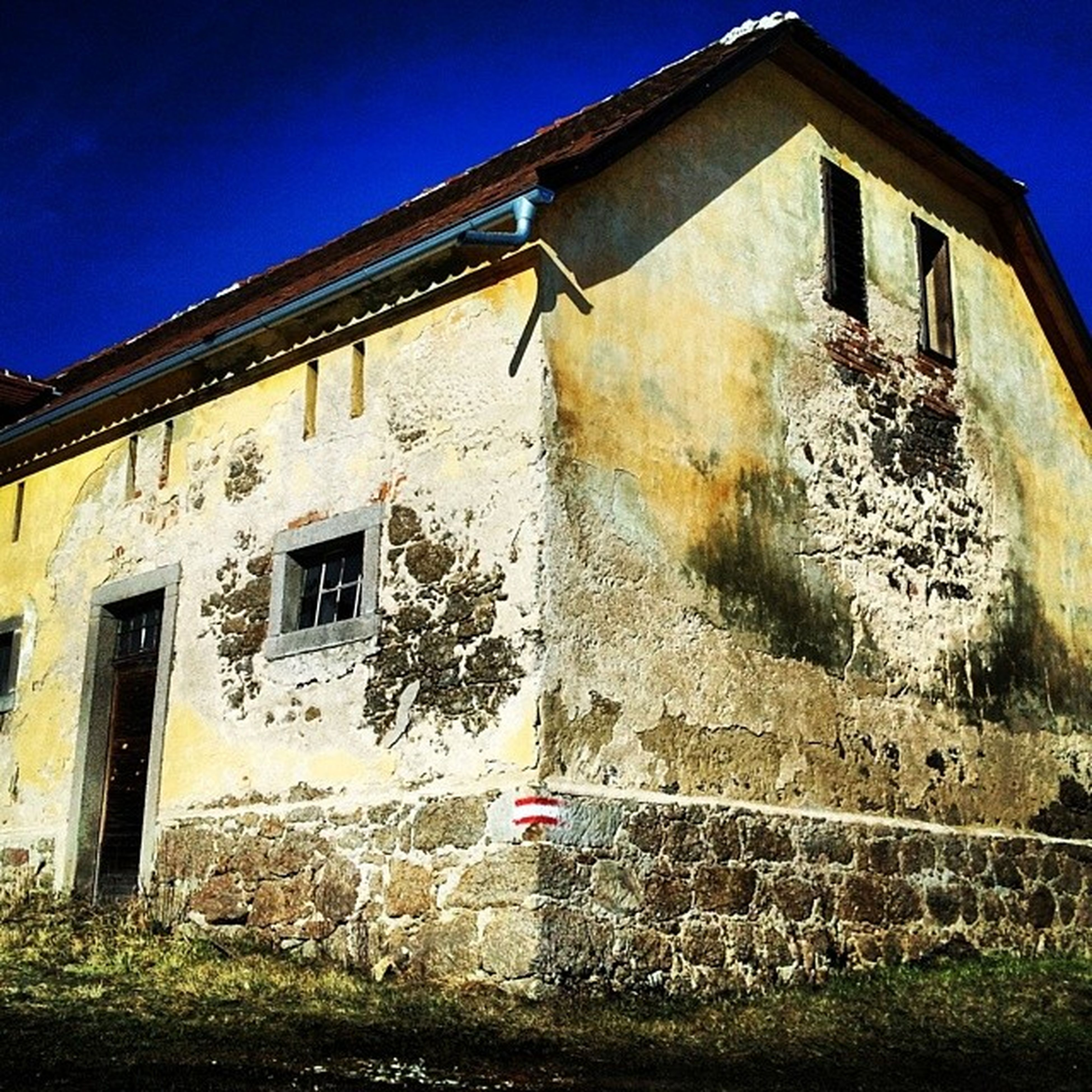 building exterior, architecture, built structure, low angle view, window, house, old, abandoned, residential structure, clear sky, weathered, blue, brick wall, obsolete, building, damaged, residential building, wall - building feature, run-down, day