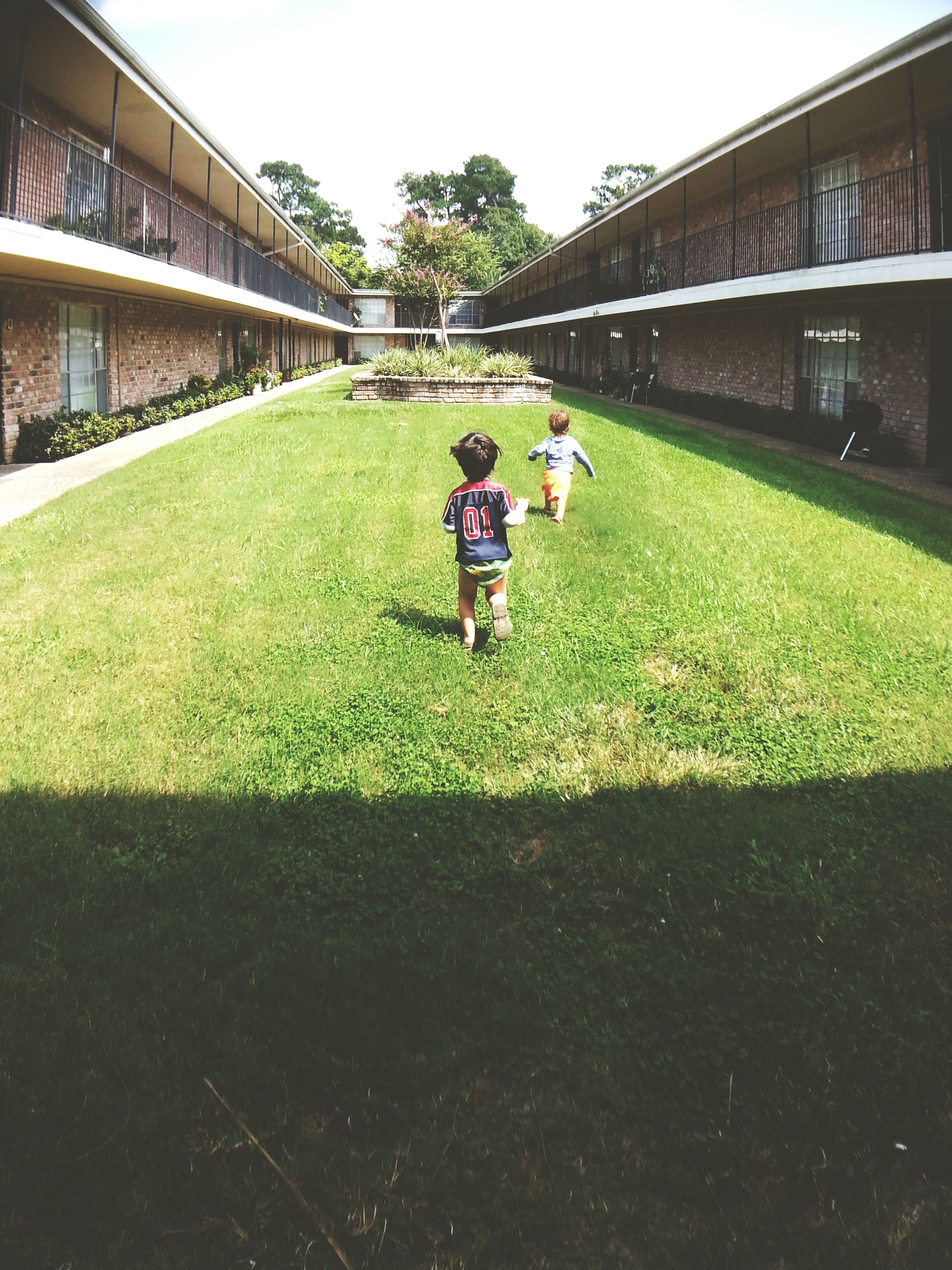 grass, building exterior, architecture, playing, built structure, childhood, green color, boys, full length, city, elementary age, toddler, day, grassy, innocence, outdoors, footpath, yard, baby boys, unknown gender