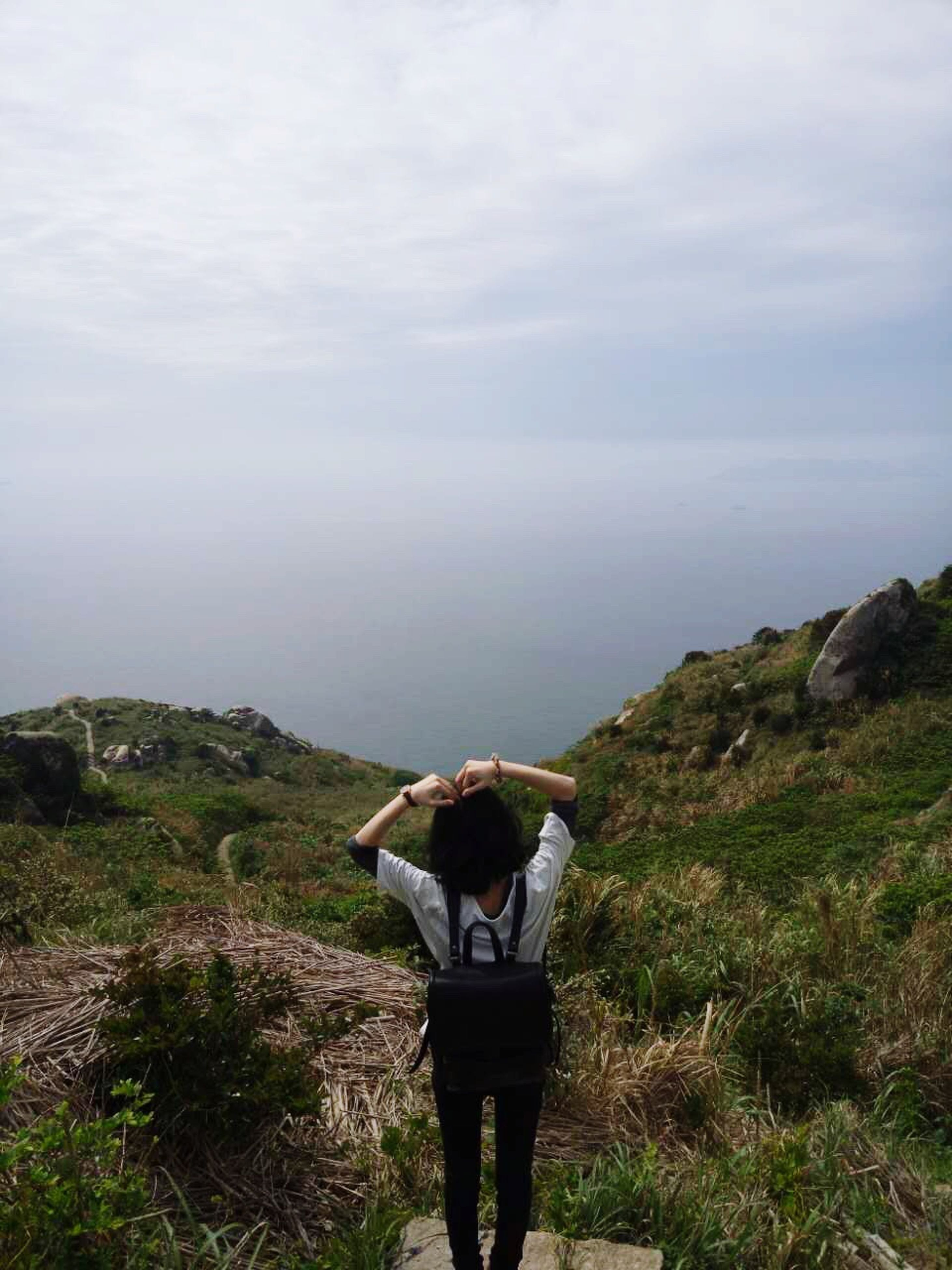 standing, rear view, lifestyles, sky, leisure activity, tranquility, tranquil scene, scenics, men, beauty in nature, nature, cloud - sky, person, mountain, casual clothing, full length, looking at view, landscape
