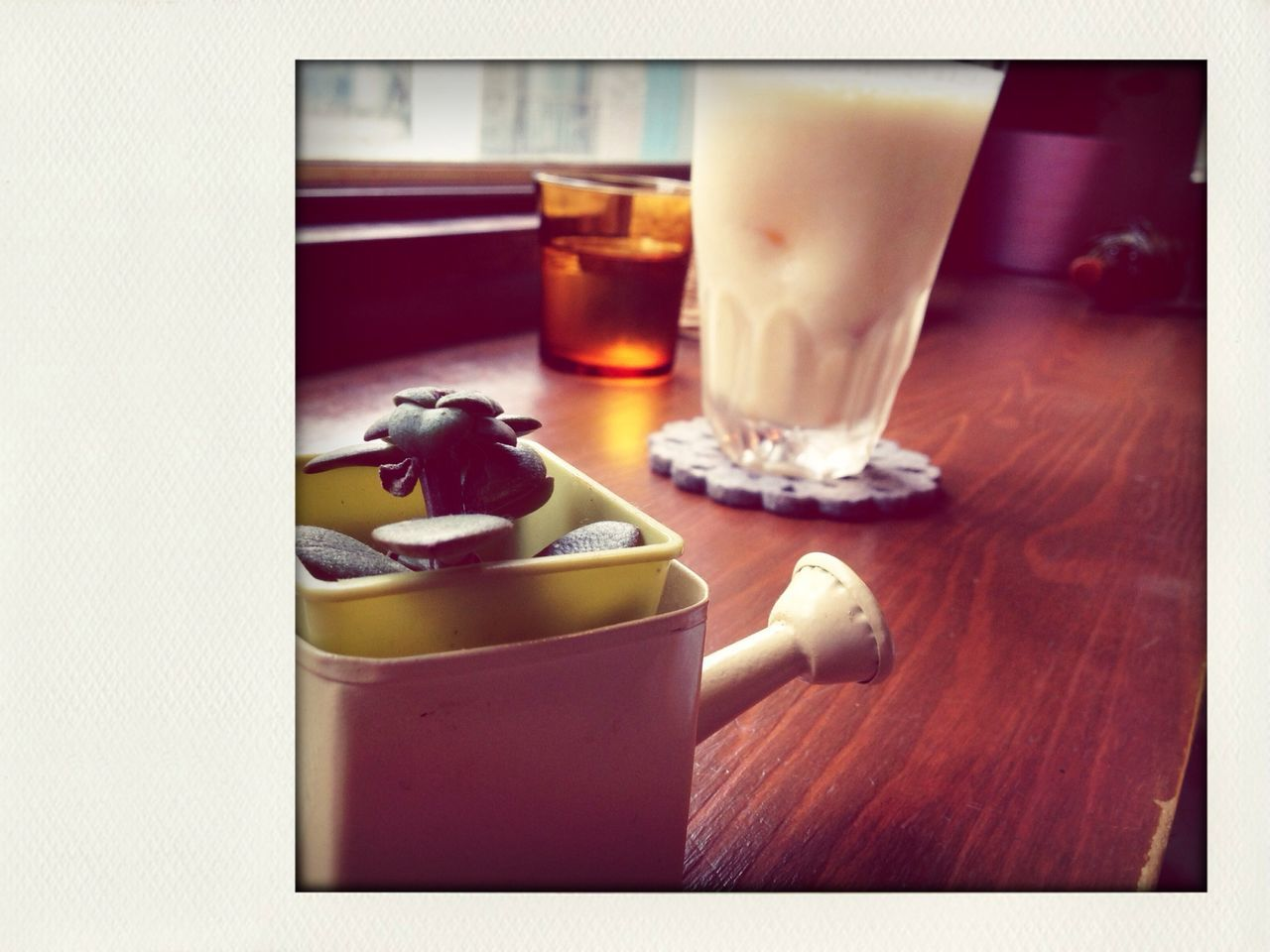 Watering can with drinks on table at cafe