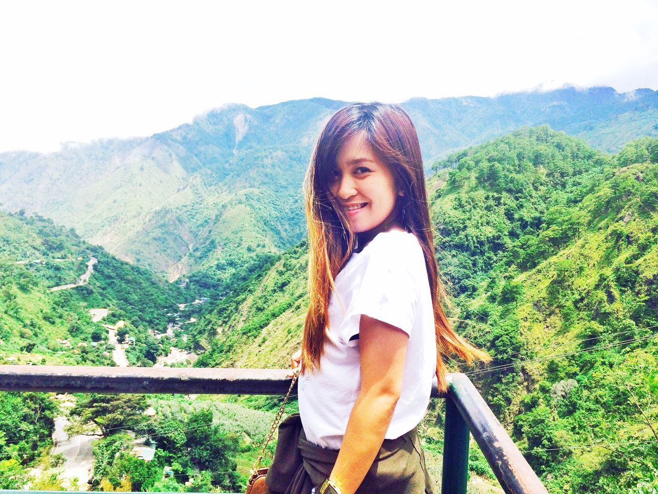 mountain, looking at camera, real people, one person, portrait, mountain range, nature, tree, casual clothing, standing, leisure activity, beauty in nature, smiling, day, scenics, lifestyles, landscape, young adult, happiness, outdoors, young women, medium-length hair, forest, sky