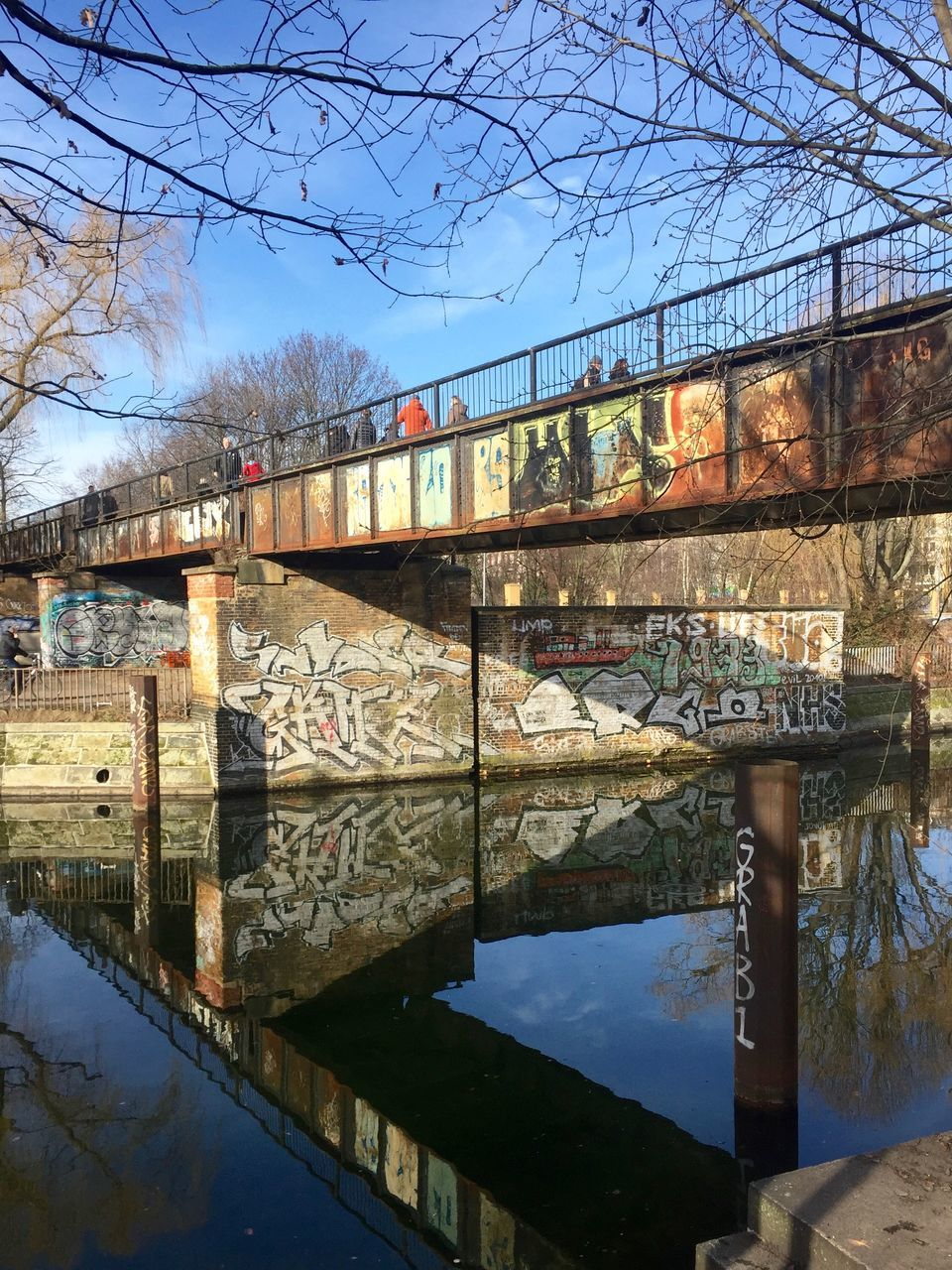 bridge - man made structure, connection, architecture, water, reflection, built structure, transportation, river, bare tree, day, bridge, tree, sky, outdoors, nature, no people, footbridge