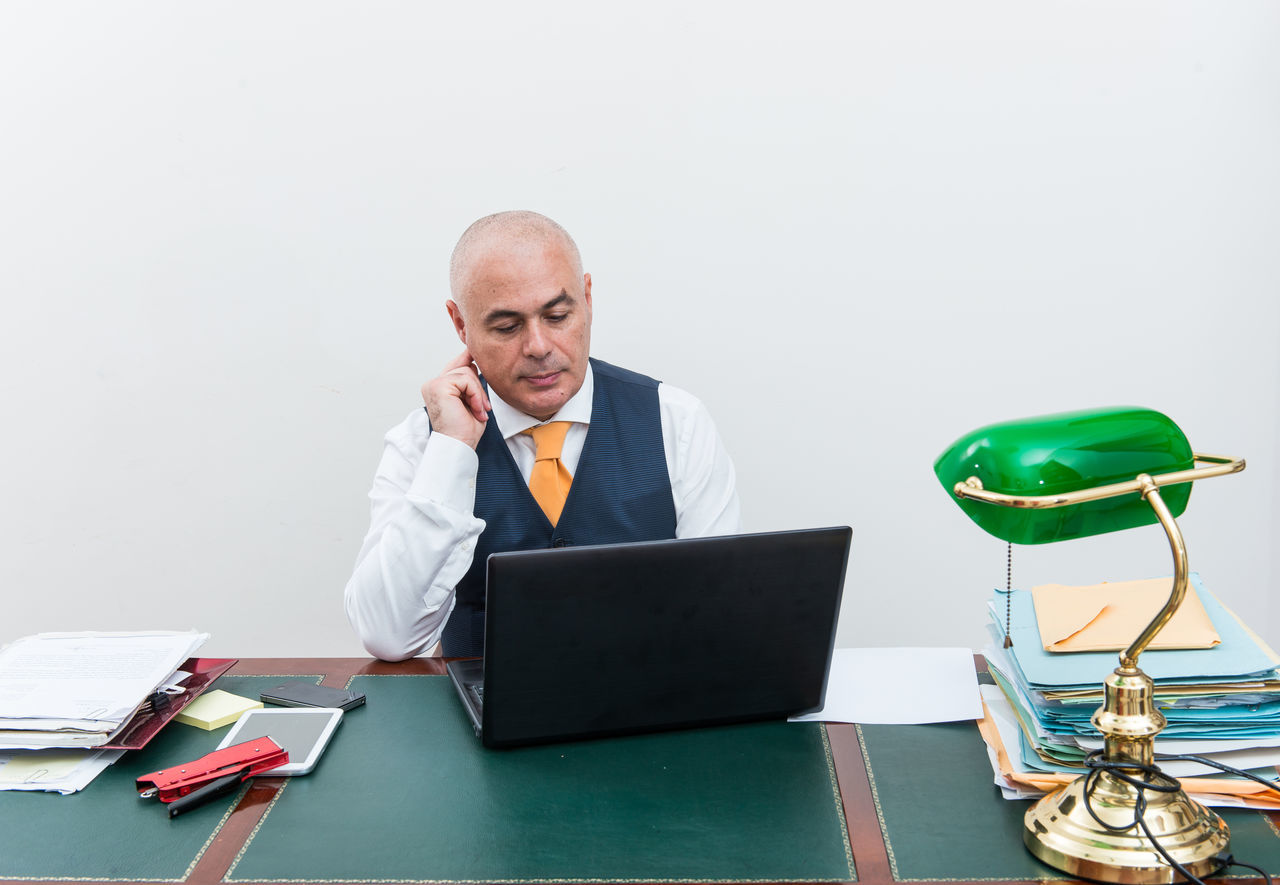 Adult Adults Only Business Business Finance And Industry Businessman Businesswear Corporate Business Desk Hair Loss Looking Down Men Occupation Office One Man Only One Person Only Men Paperwork People Sitting Table Technology Using Laptop Well-dressed Wireless Technology Working