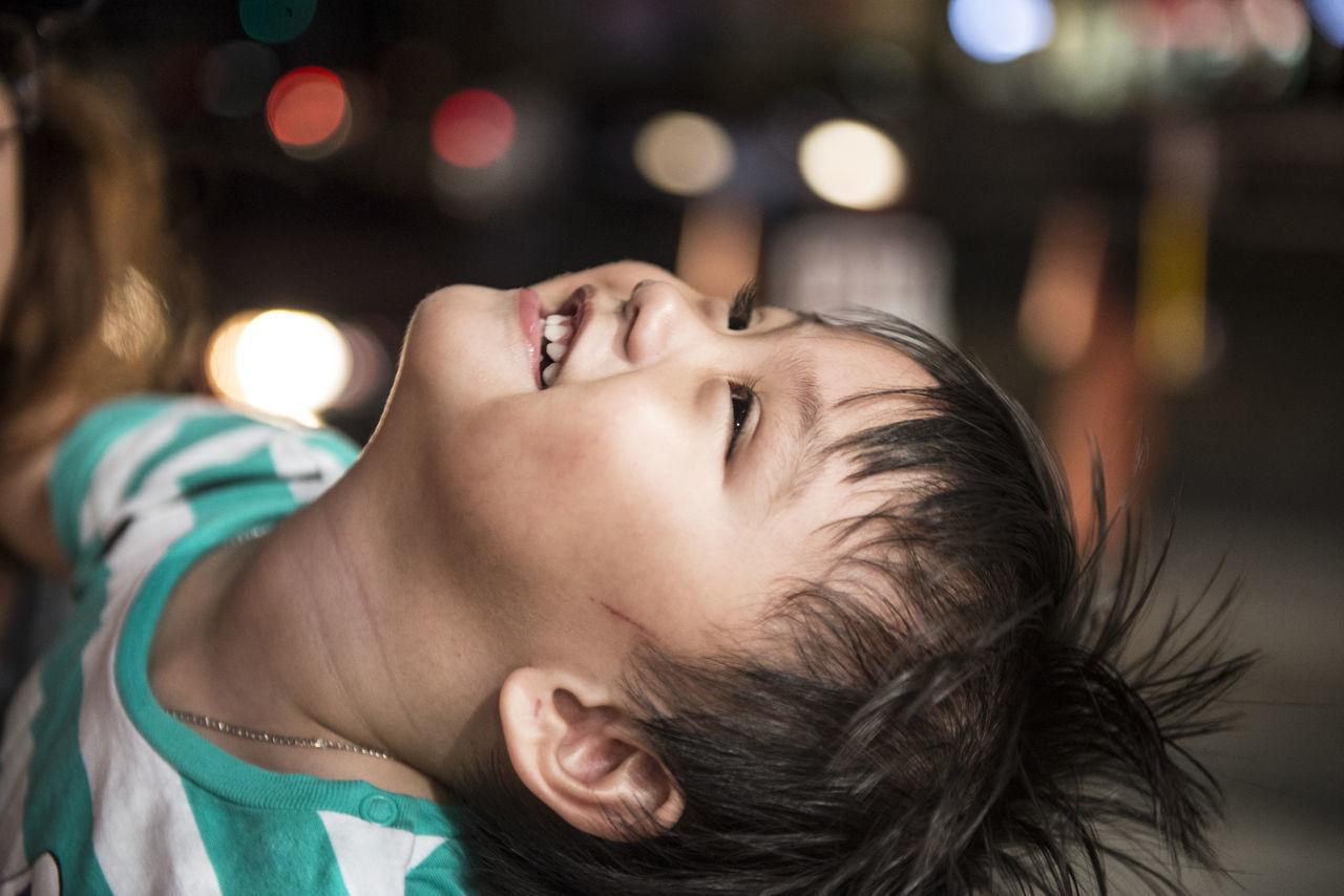 Close-Up Of Cheerful Boy Looking Up At Night