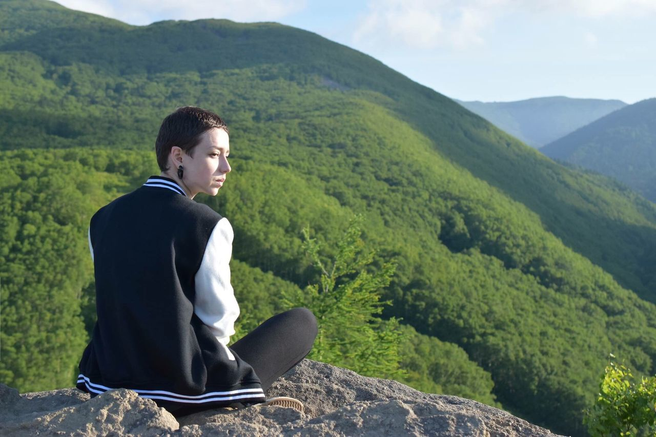 Mountain Sitting One Person Relaxation Nature Outdoors Day Landscape Full Length Tree Men Mountain Range Scenics Beauty In Nature Adult Young Adult One Man Only People Only Men Sky