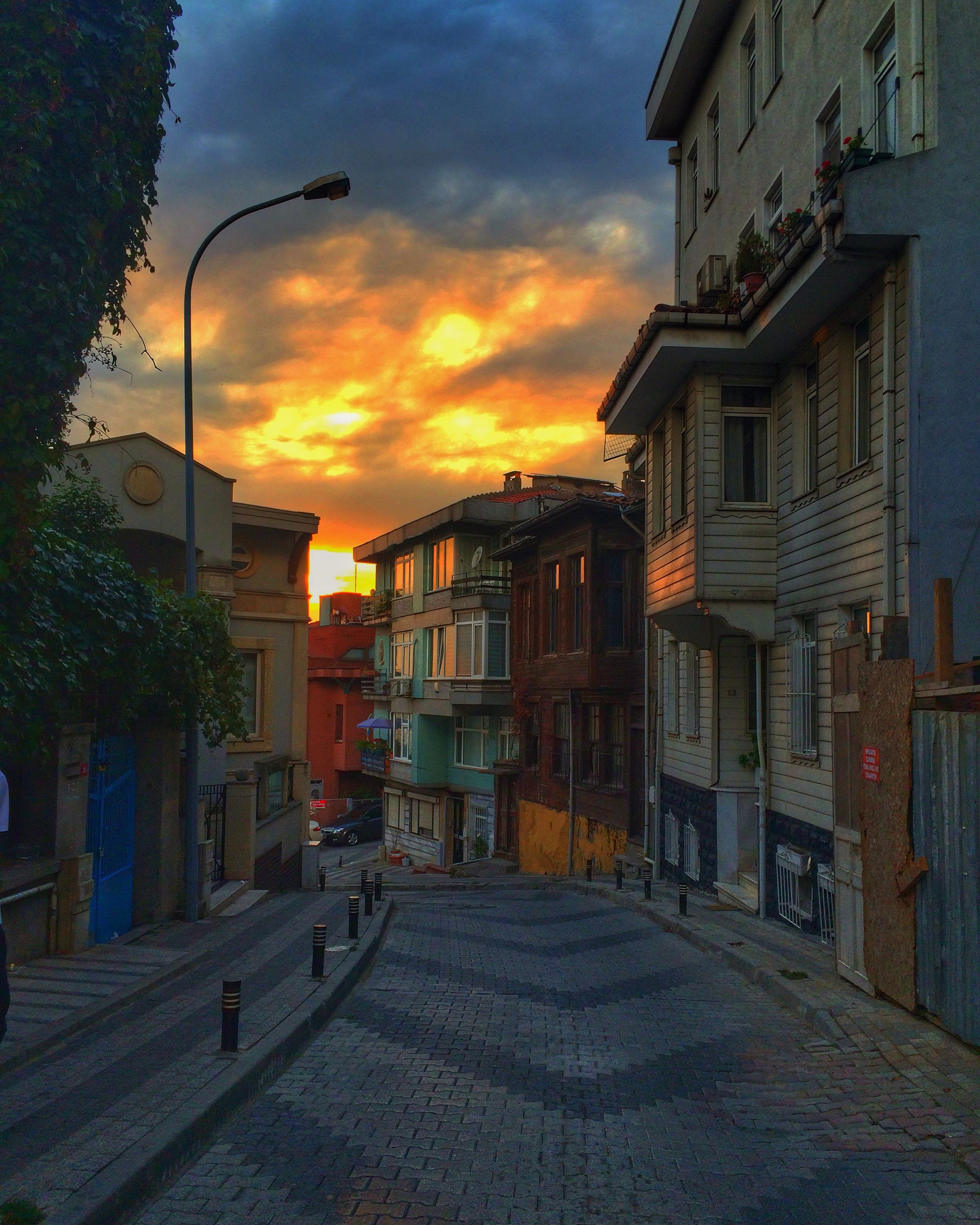 building exterior, architecture, built structure, sky, sunset, residential building, residential structure, cloud - sky, street, house, city, street light, the way forward, orange color, building, cloud, cloudy, town, outdoors, road