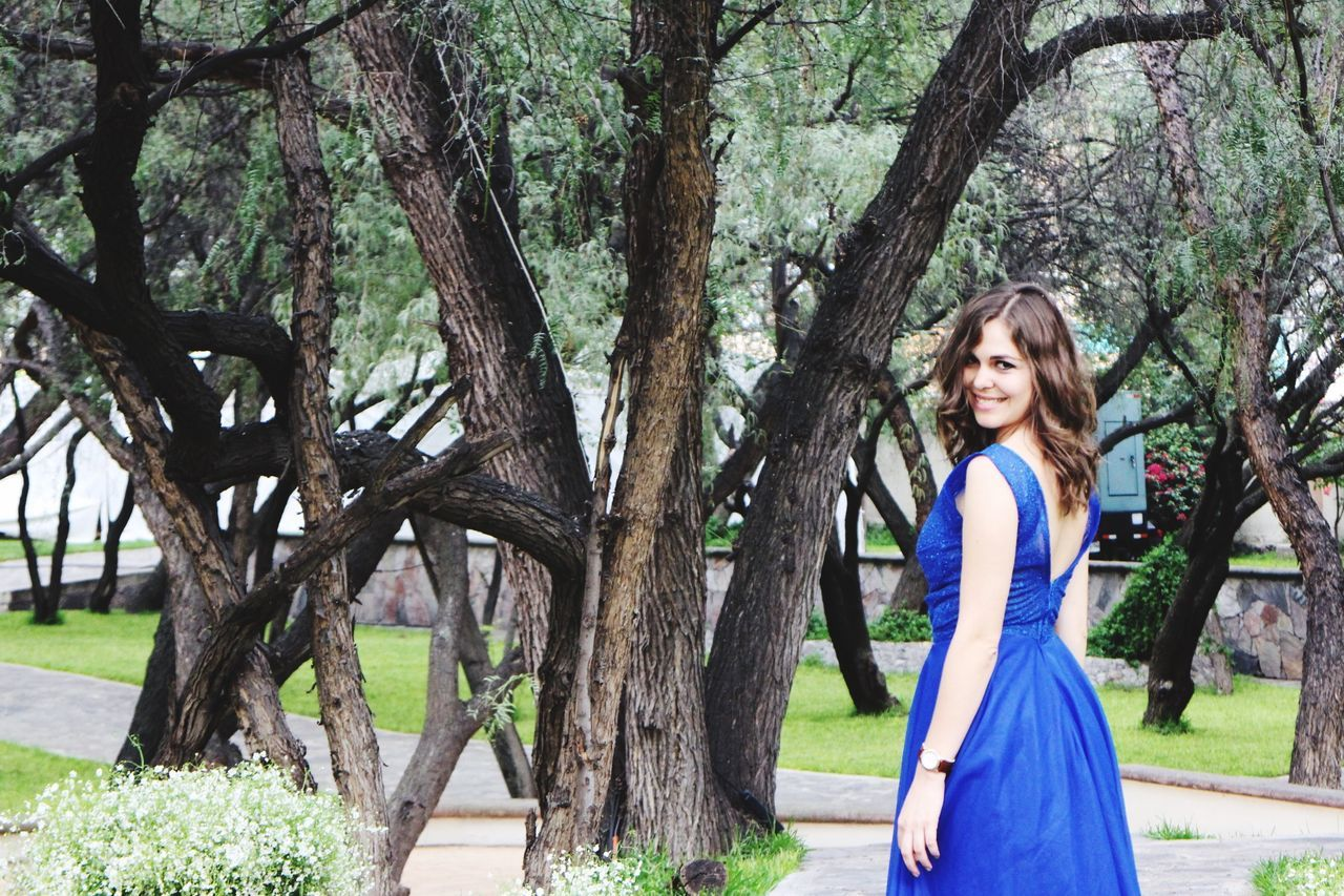 tree, tree trunk, dress, one person, long hair, smiling, happiness, young adult, standing, beautiful woman, brown hair, outdoors, beauty, side view, day, looking at camera, young women, nature, branch, portrait, one young woman only, adult, one woman only, beautiful people, cheerful, full length, only women, adults only, beauty in nature, people
