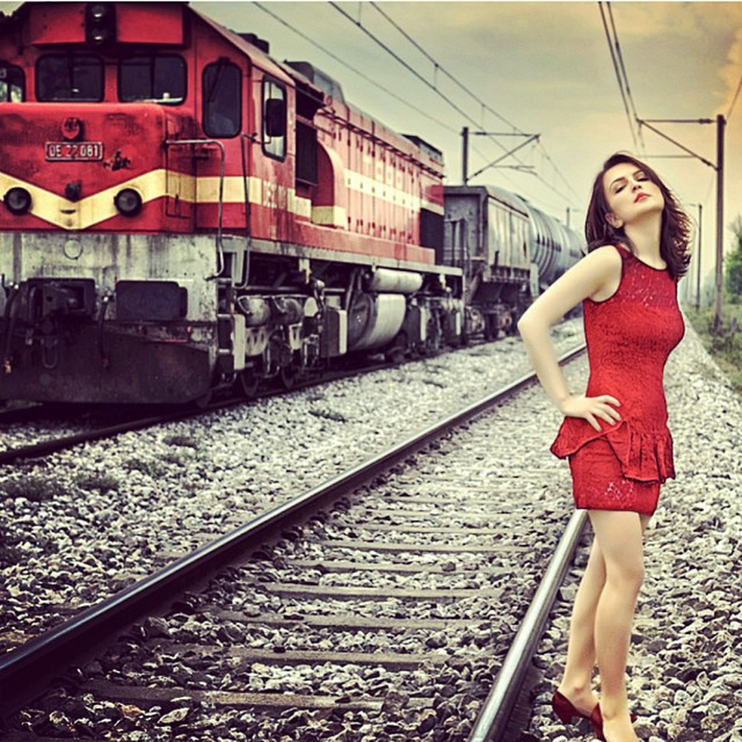 railroad track, rail transportation, transportation, public transportation, railroad station platform, travel, lifestyles, mode of transport, train - vehicle, railroad station, train, passenger train, casual clothing, standing, leisure activity, full length, built structure, red