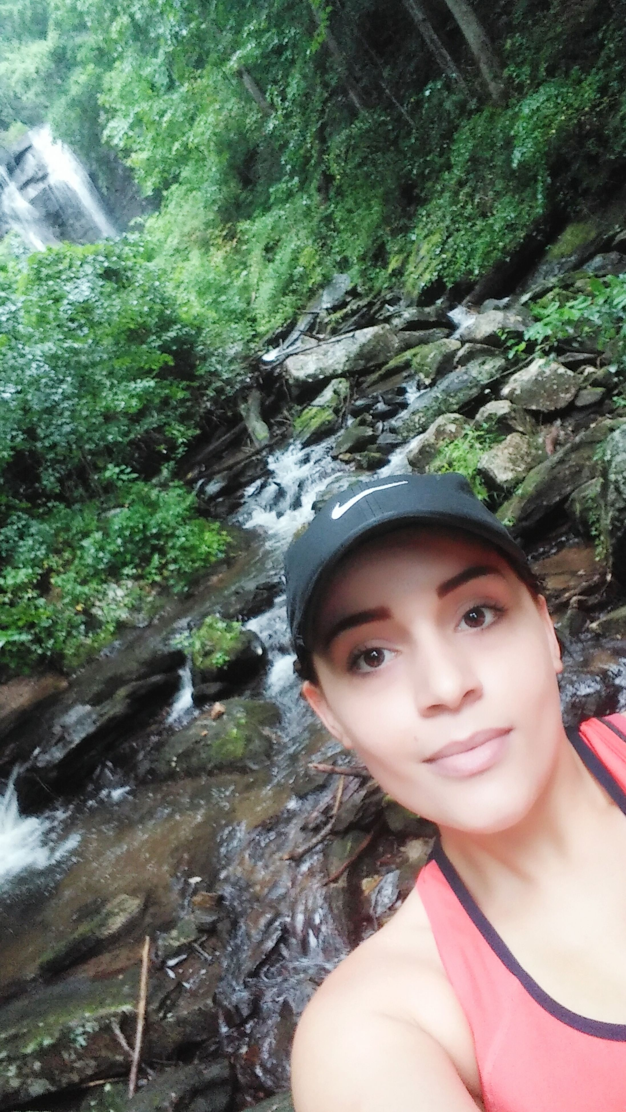 leisure activity, looking at camera, lifestyles, headshot, portrait, young adult, smiling, front view, young women, forest, tree, person, day, water, scenics, nature, outdoors, black hair, content, green color, focus on foreground