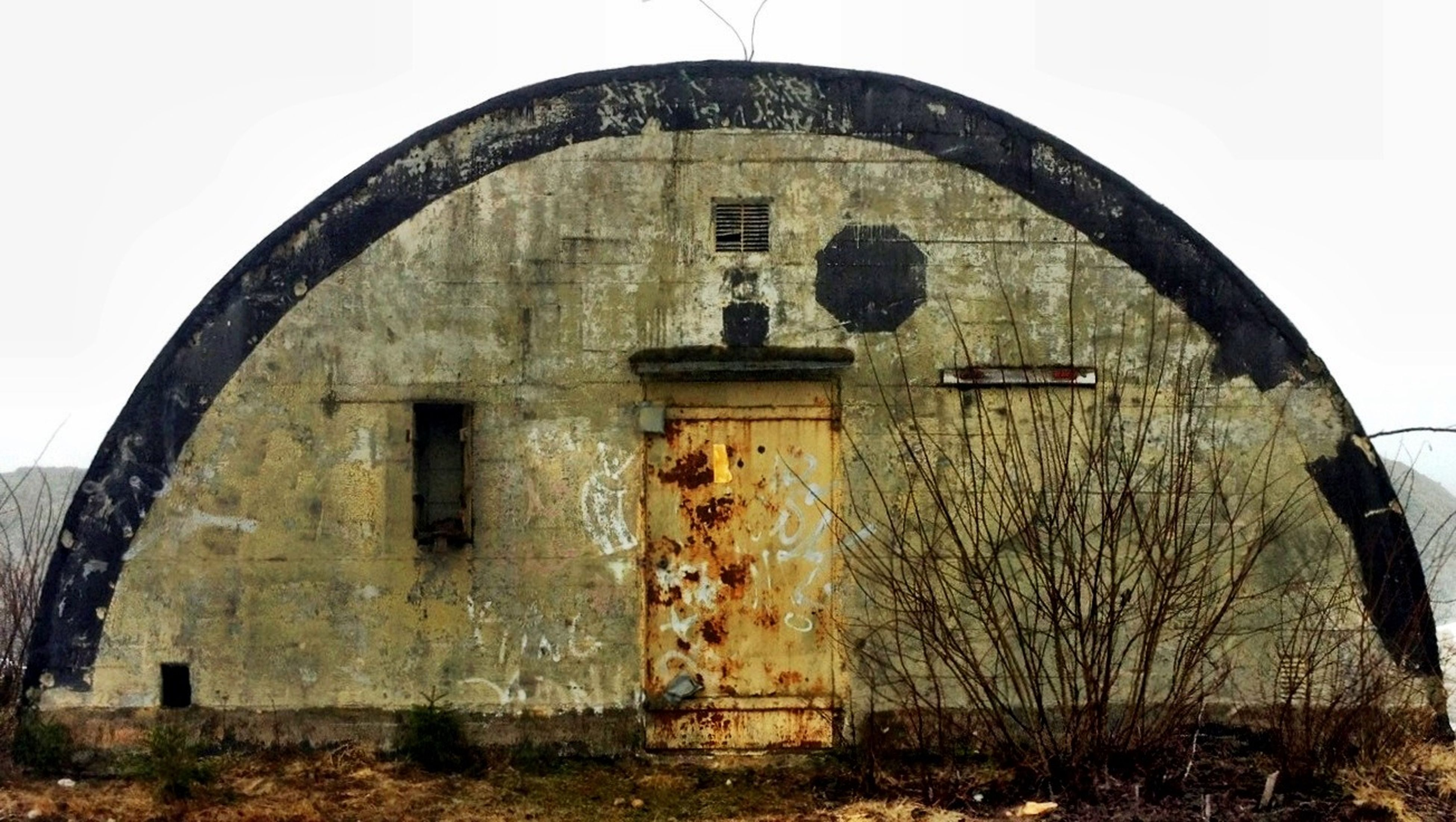 architecture, built structure, building exterior, arch, old, abandoned, house, window, obsolete, weathered, damaged, run-down, sky, clear sky, low angle view, tree, day, wall - building feature, bare tree, outdoors