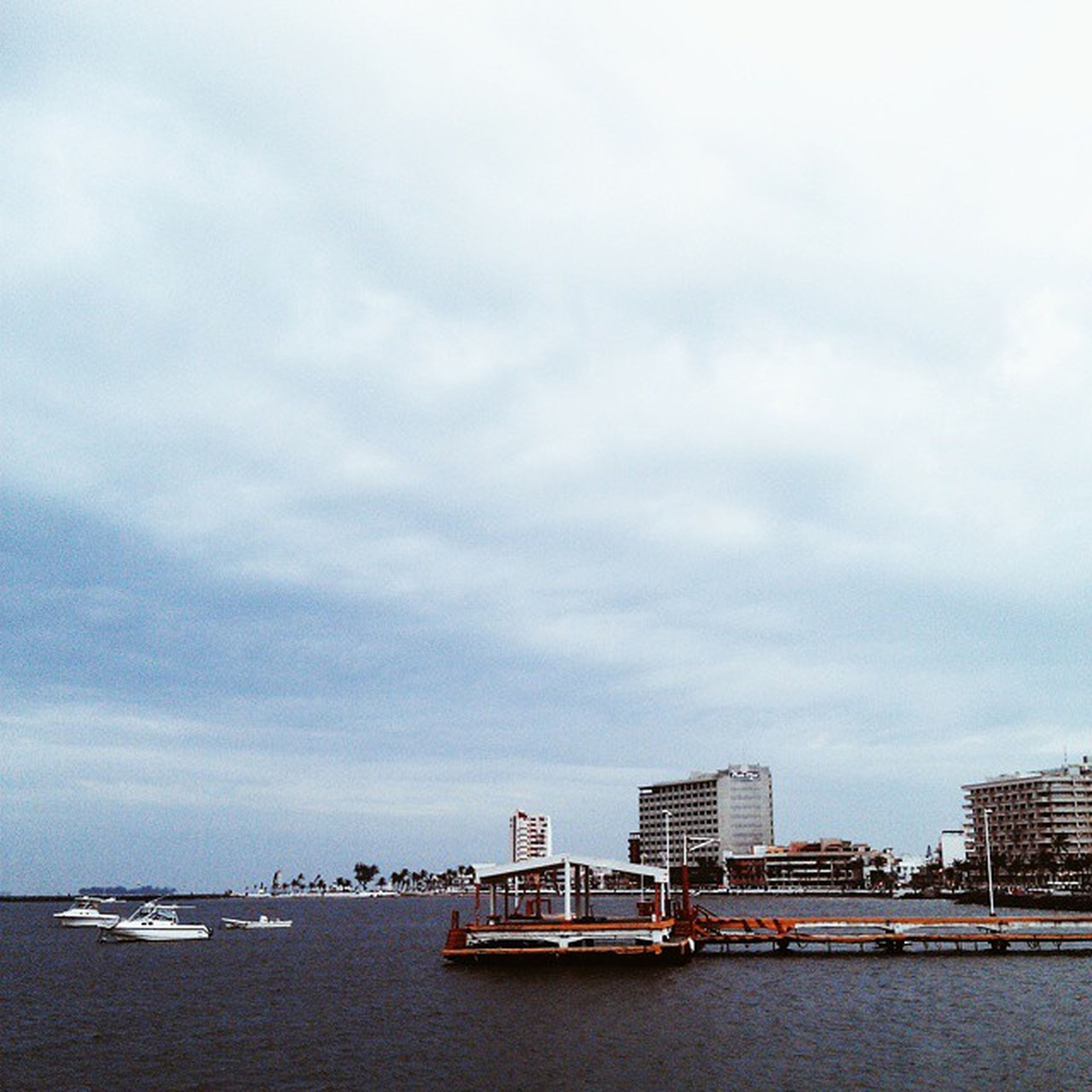 water, waterfront, sea, sky, architecture, built structure, building exterior, nautical vessel, city, cloud - sky, transportation, cloudy, river, mode of transport, day, harbor, cloud, nature, outdoors, cityscape