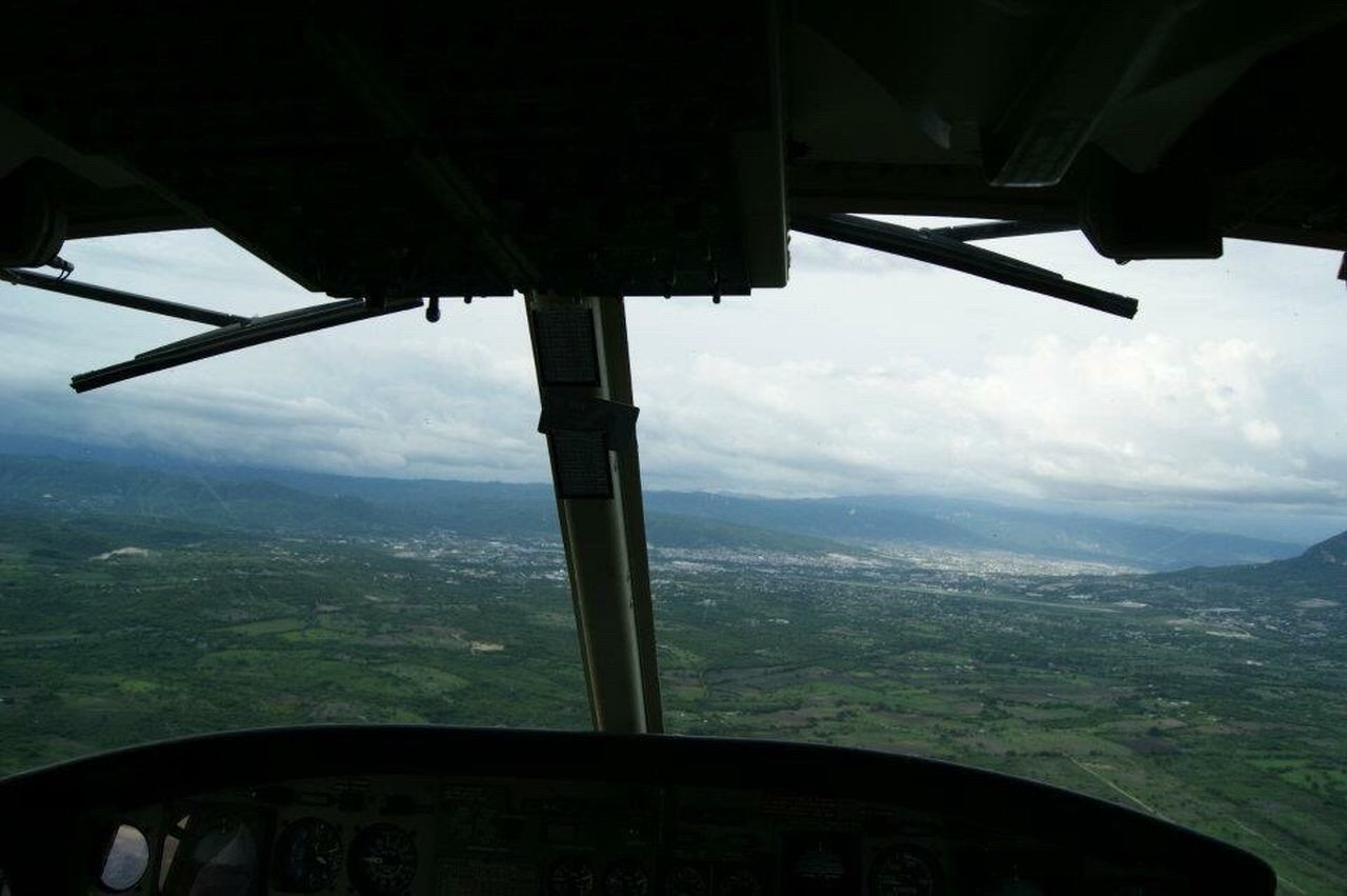 vehicle interior, mountain, landscape, scenics, air vehicle, airplane, transportation, sky, window, day, aerial view, cloud - sky, nature, mode of transport, mid-air, beauty in nature, flying, mountain range, tranquil scene, journey, tranquility, no people, travel, vehicle part, indoors, cockpit, airplane wing