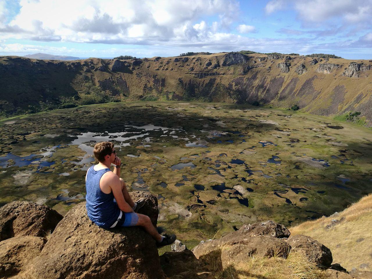 High Angle View Of Hiker Looking At View While Sitting At Crater Lake Of Rano Kau