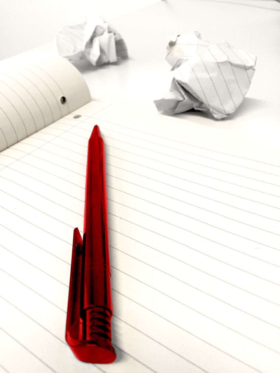 Close-Up Of Red Pen Over Book By Crumpled Pages On Table