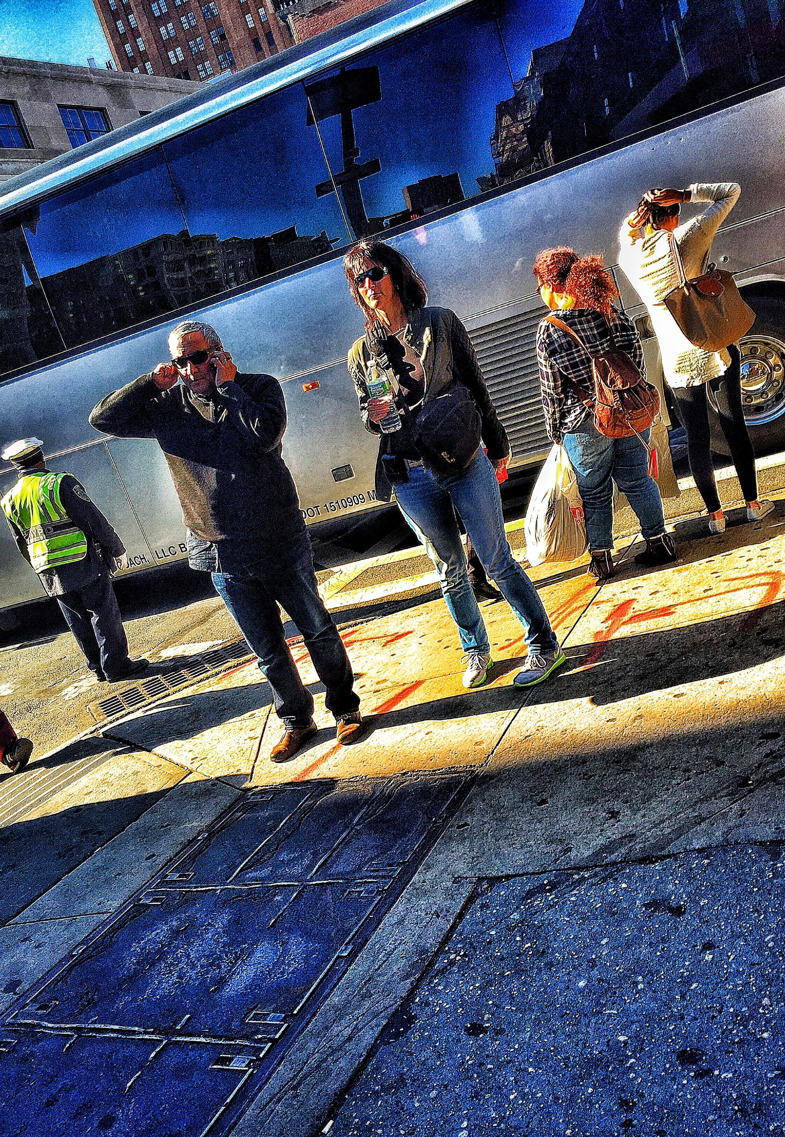 high angle view, street, shadow, sunlight, lifestyles, road, outdoors, graffiti, leisure activity, day, architecture, human representation, built structure, sidewalk, men, building exterior, art, standing