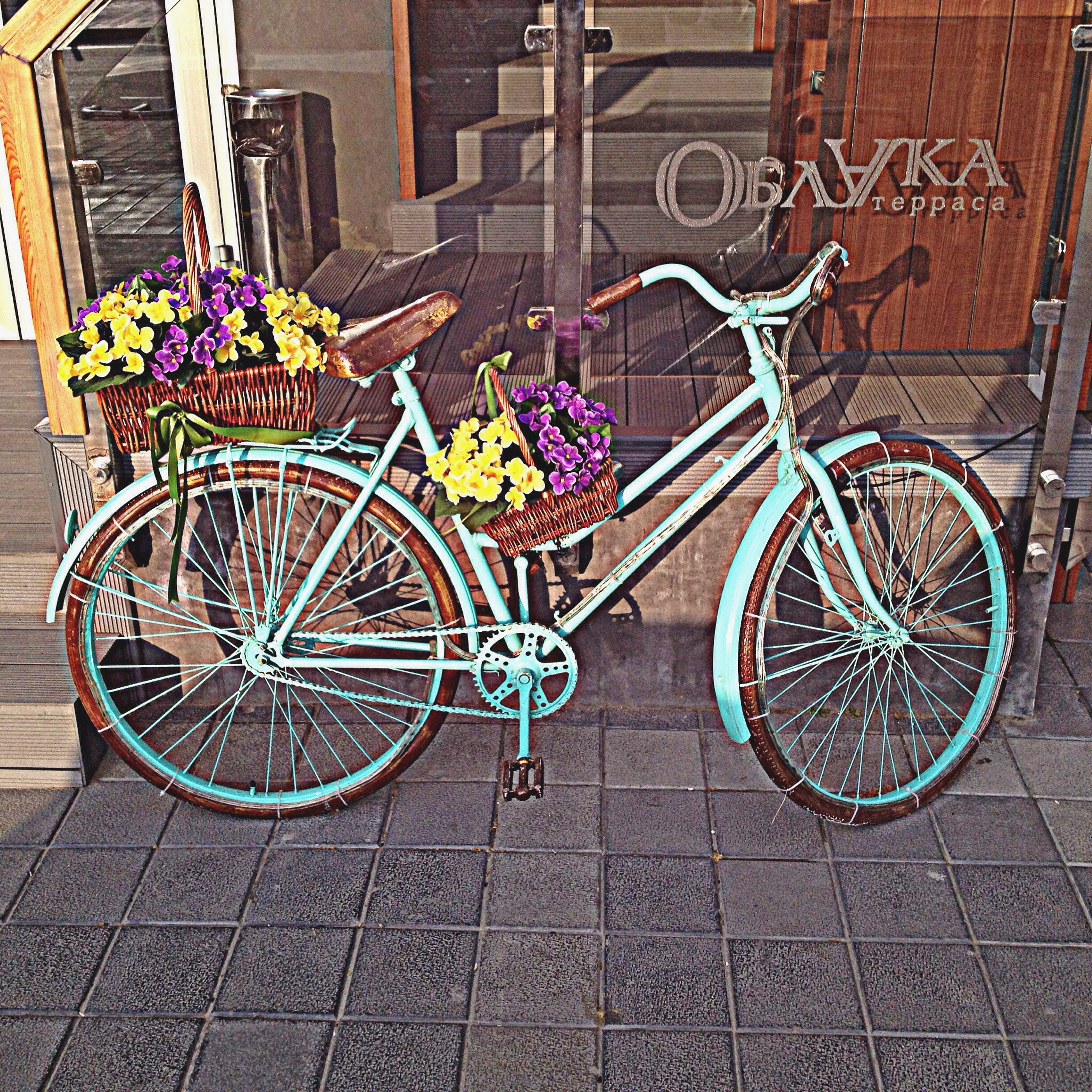 bicycle, flower, built structure, architecture, building exterior, sidewalk, wall - building feature, transportation, potted plant, multi colored, cobblestone, plant, parking, paving stone, stationary, no people, day, street, outdoors, mode of transport