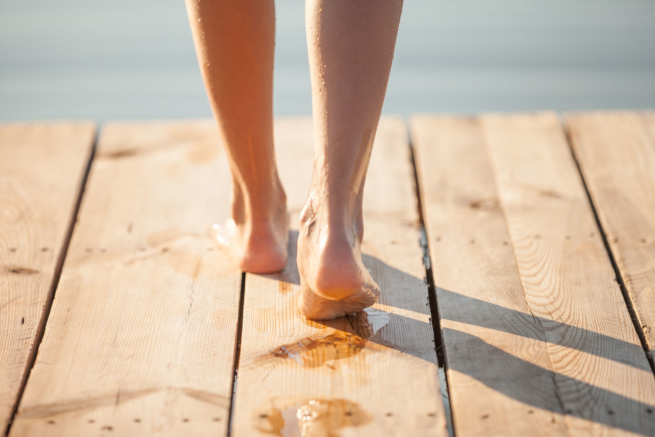 Low Section Of Wet Woman On Wooden Jetty