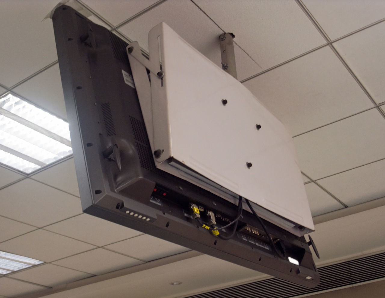 In large auditoriums / presentation rooms, there are LCD televisions hanging from the roof so that people sitting near the rear of the room can also see the presentation Electronics  Hanging TV Indoors  Overhead Television Projection Screen Television Television Set Tv