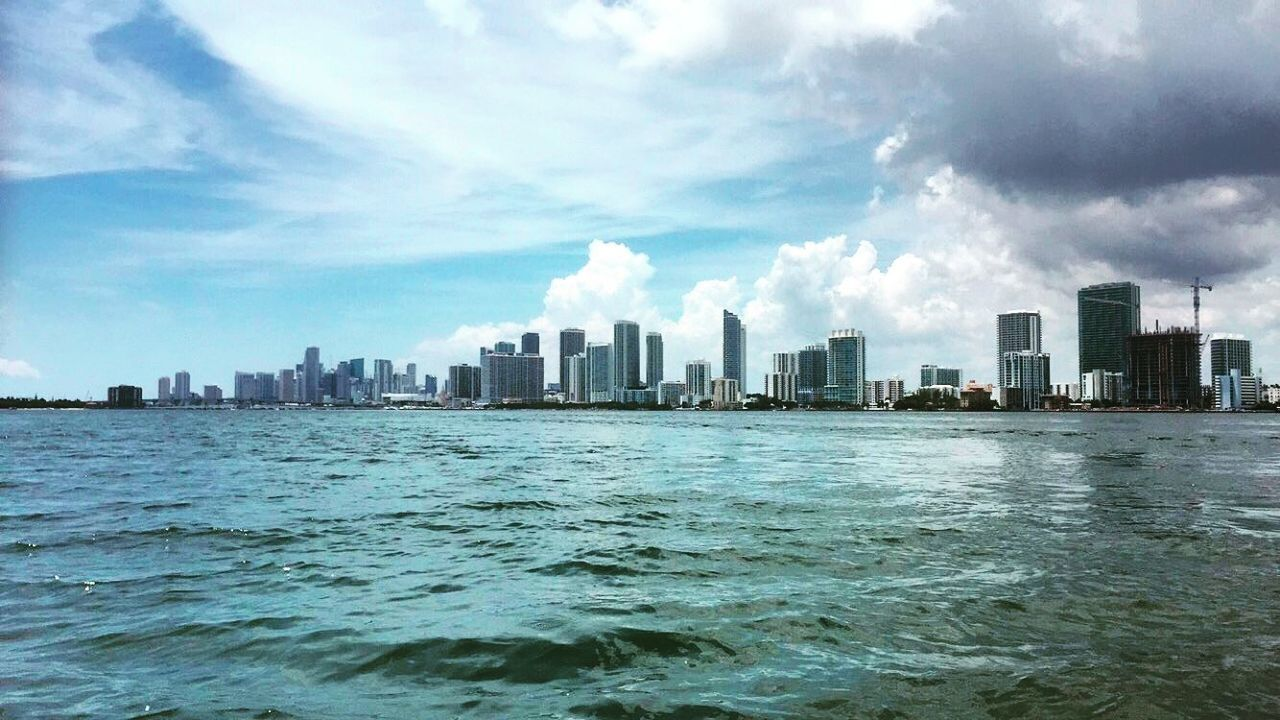 city, skyscraper, cityscape, architecture, sky, modern, building exterior, urban skyline, downtown district, waterfront, cloud - sky, sea, water, built structure, no people, outdoors, day