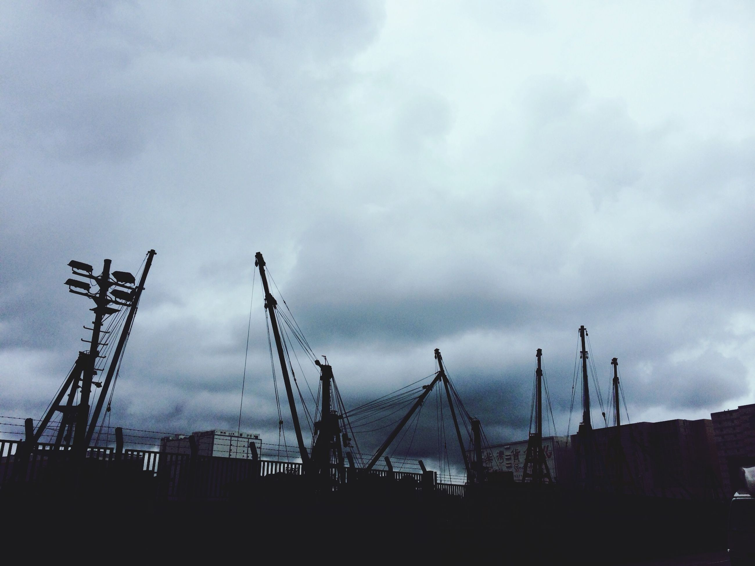 sky, building exterior, architecture, built structure, cloud - sky, low angle view, cloudy, silhouette, cloud, dusk, city, building, overcast, weather, outdoors, no people, development, residential structure, house, construction site