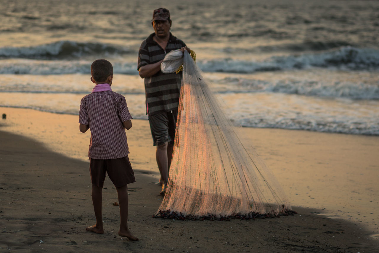 A boy is watching a fisherman at sunset, Cochin, India Beach Beach Life Boy Boys Cochin Family Fisherman Fishermen Fishing Net India Indian Learning Leisure Activity Males  Offspring Sand Son Sunset Teenager Togetherness Two People Watching Waves