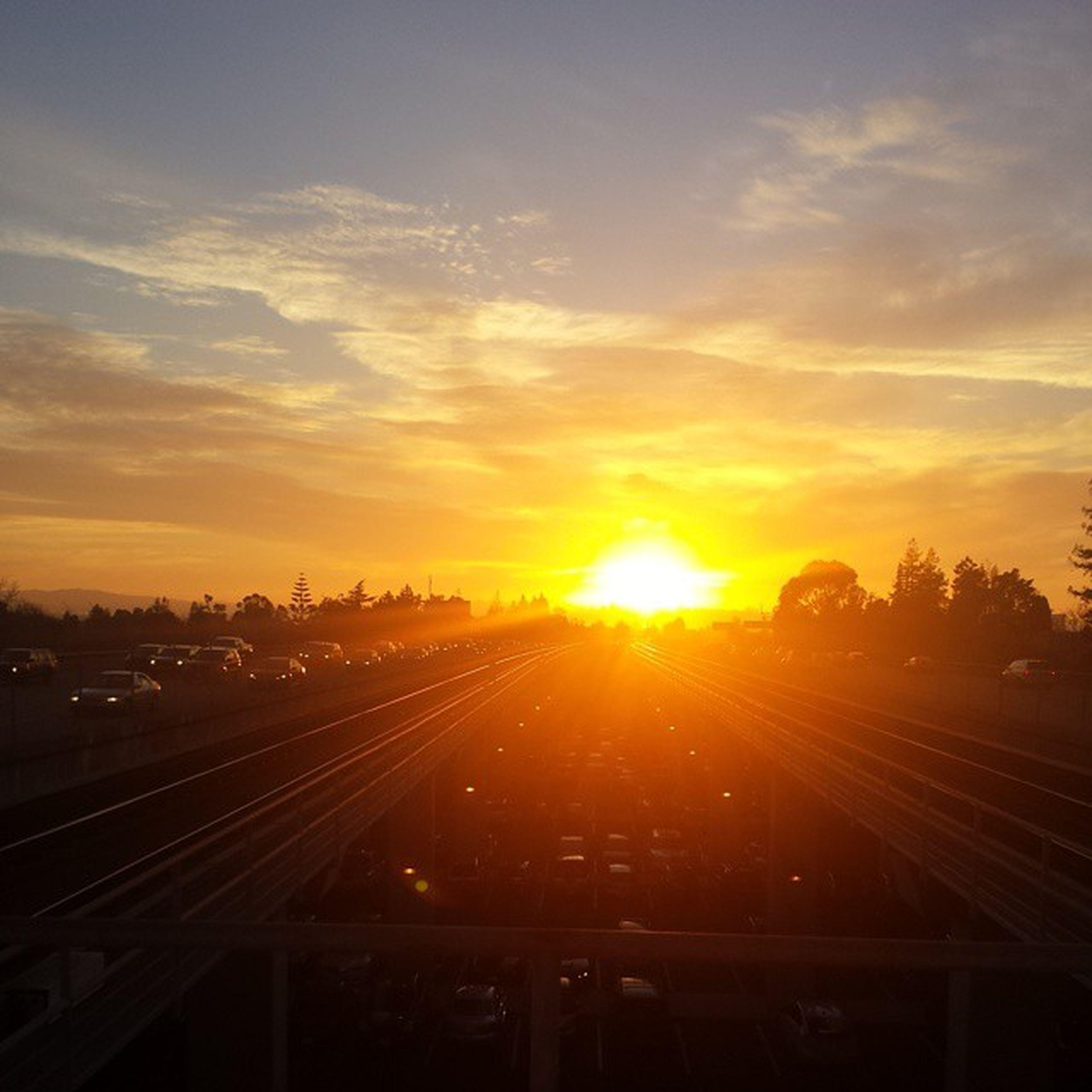 transportation, sunset, sky, railroad track, the way forward, road, sun, diminishing perspective, cloud - sky, vanishing point, lens flare, sunbeam, orange color, mode of transport, sunlight, rail transportation, car, land vehicle, on the move, silhouette