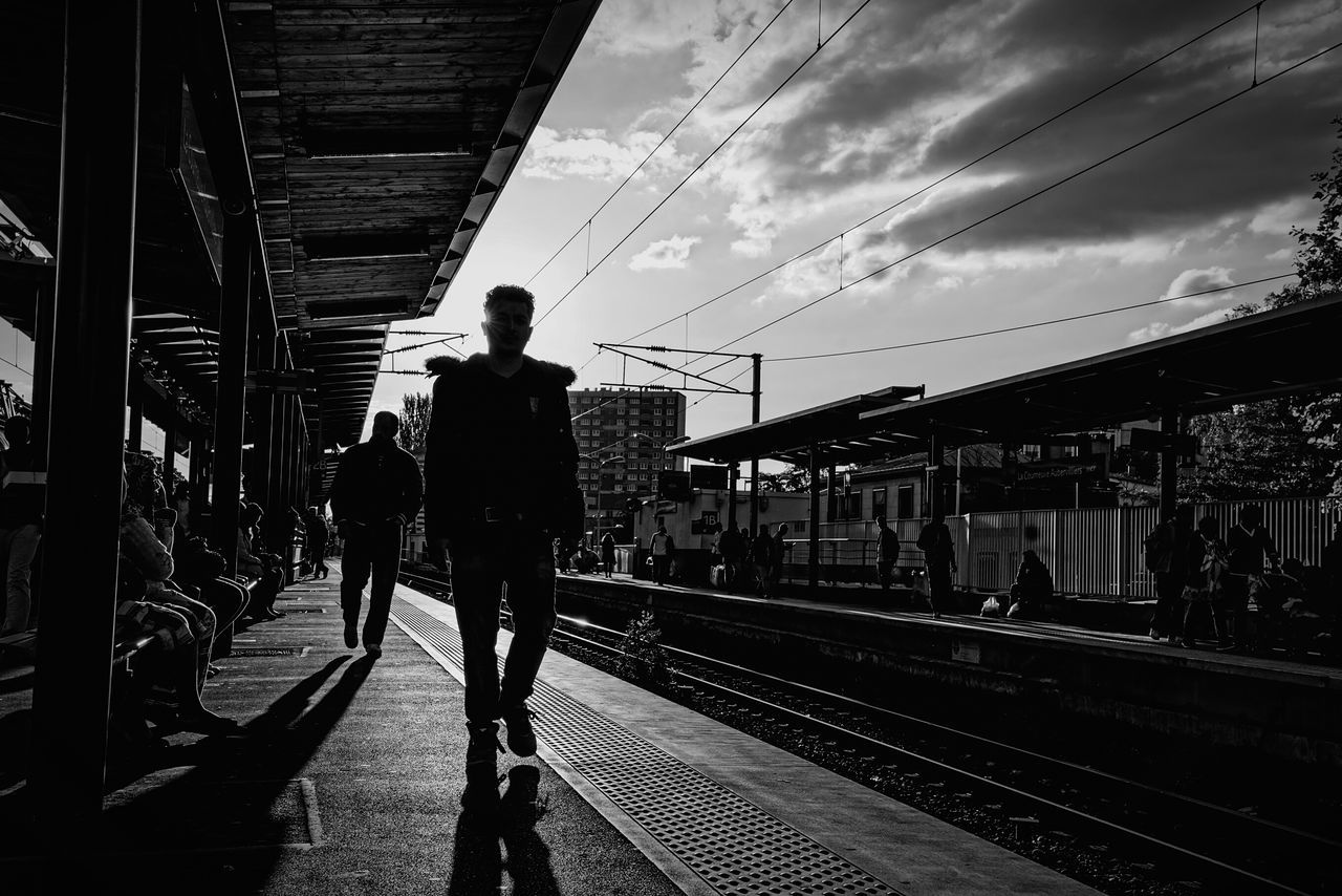 railroad track, transportation, railroad station platform, rail transportation, real people, railroad station, sky, public transportation, men, built structure, full length, architecture, silhouette, lifestyles, outdoors, day, station, women, city, people