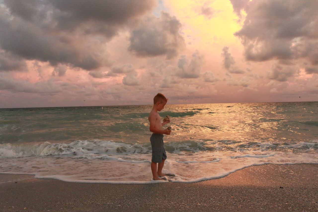Beach Beauty In Nature Boys Childhood Cloud - Sky Full Length Horizon Over Water Leisure Activity Lifestyles Nature One Person Outdoors Real People Rear View Sand Scenics Sea Shirtless Sky Standing Sunset Vacations Water Water_collection Wave
