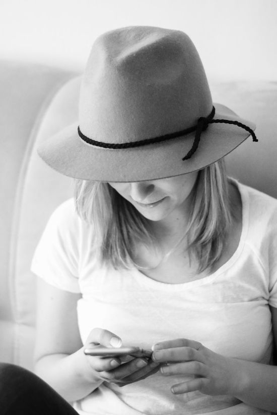B&w Photo B&w Photography B&W Portrait Blackandwhite Chatting Close-up Hat Indoors  Intimate Looking Down Monochrome Monochrome Photography Portrait Of A Woman Real People Sitting Softness Texting Young Women