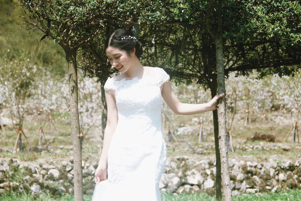 wedding, wedding dress, bride, young adult, happiness, white color, tree, one young woman only, standing, wife, young women, only women, outdoors, day, one person, one woman only, smiling, adult, life events, cheerful, well-dressed, adults only, beautiful woman, married, nature, people