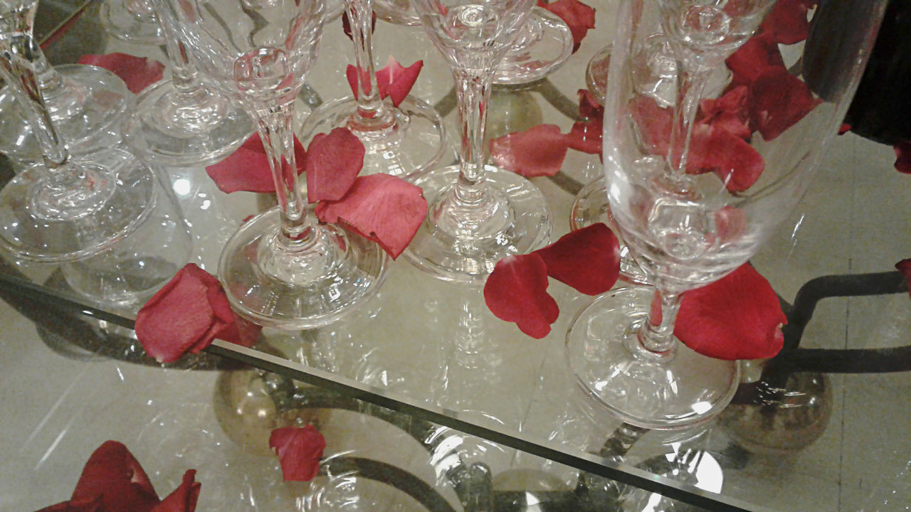 Champagne glasses set up for dining, with red rose petals. Beverage Champagne Glasses Glasses Light Rose Petals Table Setting Close-up Dining High Angle View Indoors  Large Group Of Objects Luxury No People Red Wine