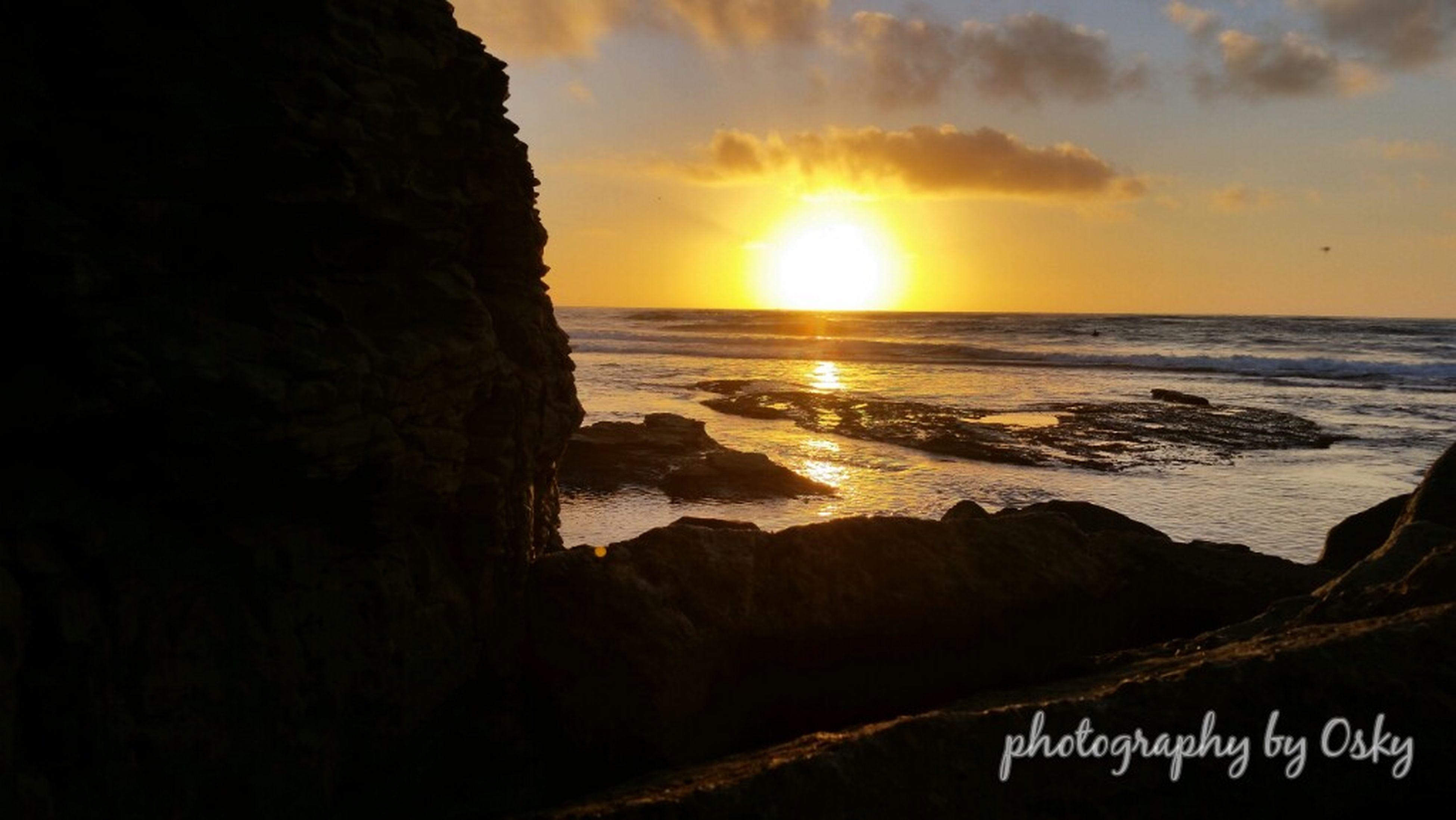 sunset, sea, horizon over water, water, scenics, tranquil scene, beauty in nature, tranquility, sky, beach, sun, shore, nature, orange color, idyllic, rock - object, cloud - sky, sunlight, remote, non-urban scene