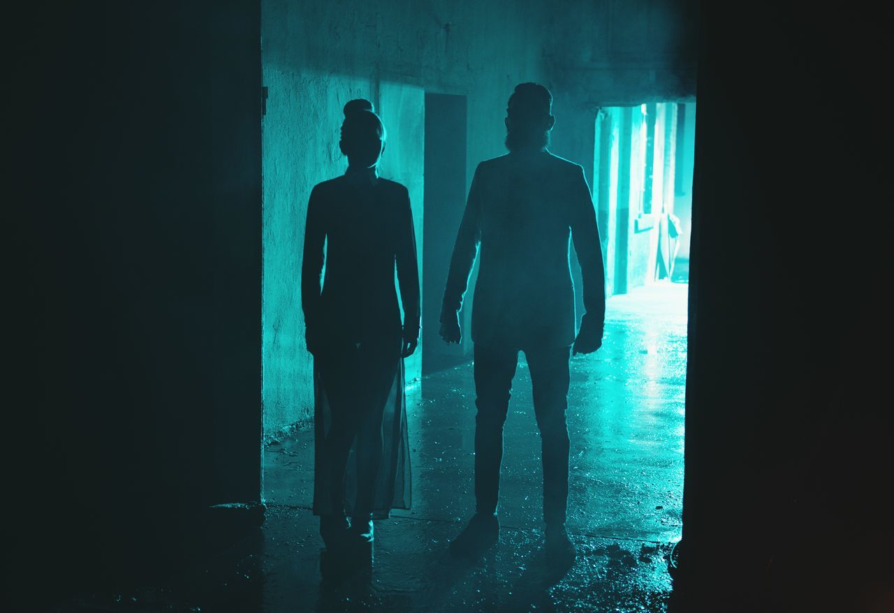 Silhouette Man And Woman Standing In Tunnel