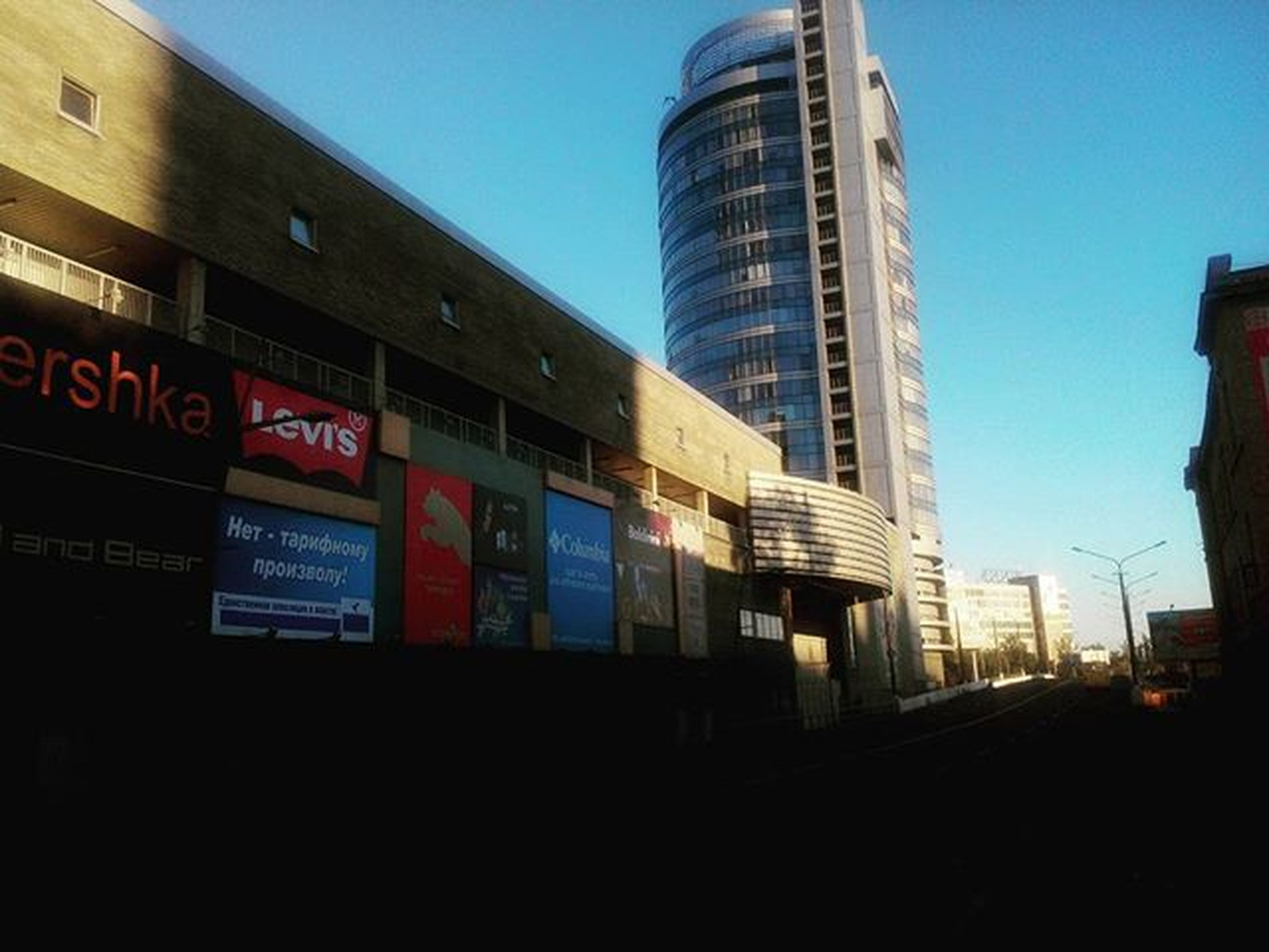 architecture, built structure, building exterior, clear sky, city, blue, modern, text, communication, low angle view, office building, western script, tower, skyscraper, building, tall - high, sky, city life, outdoors, no people