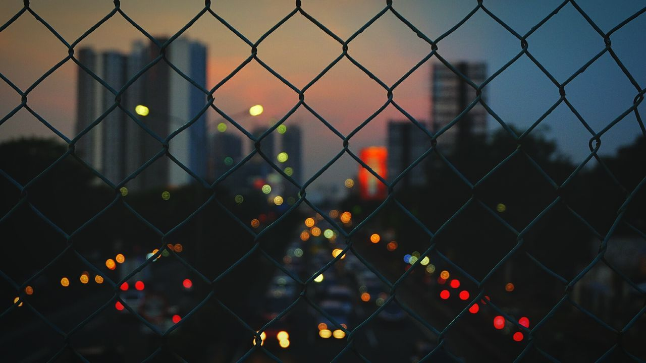 """The City Light """" The city is never sleep """" Chainlink Fence Safety Illuminated Outdoors Focus On Foreground Protection Sky Close-up Security No People Landscape Like Followme Follow4follow Instagram Respost EyeEm Best Shots EyeEm Gallery Fujifilm Terfujilah Fujifilm_xseries 50mm Bokeh Bokeh Lights"""