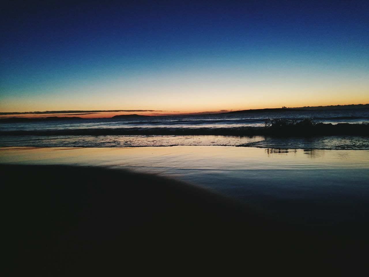 tranquility, tranquil scene, scenics, nature, water, beauty in nature, copy space, no people, reflection, outdoors, sunset, sky, silhouette, blue, clear sky, sea, beach, day