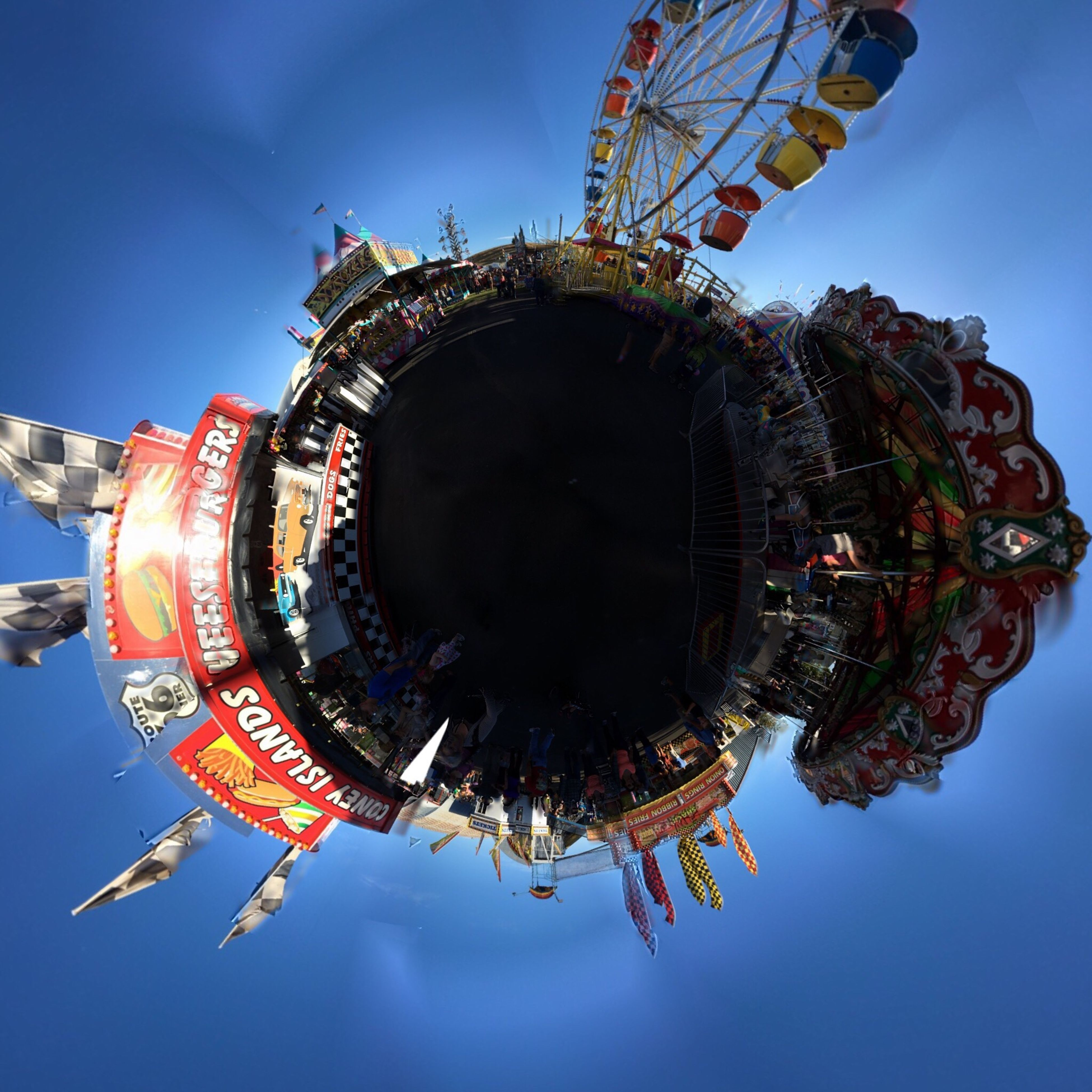 sky, fish-eye lens, clear sky, architecture, amusement park, outdoors, built structure, blue, building exterior, low angle view, day, no people, amusement park ride, skyscraper, water, cityscape