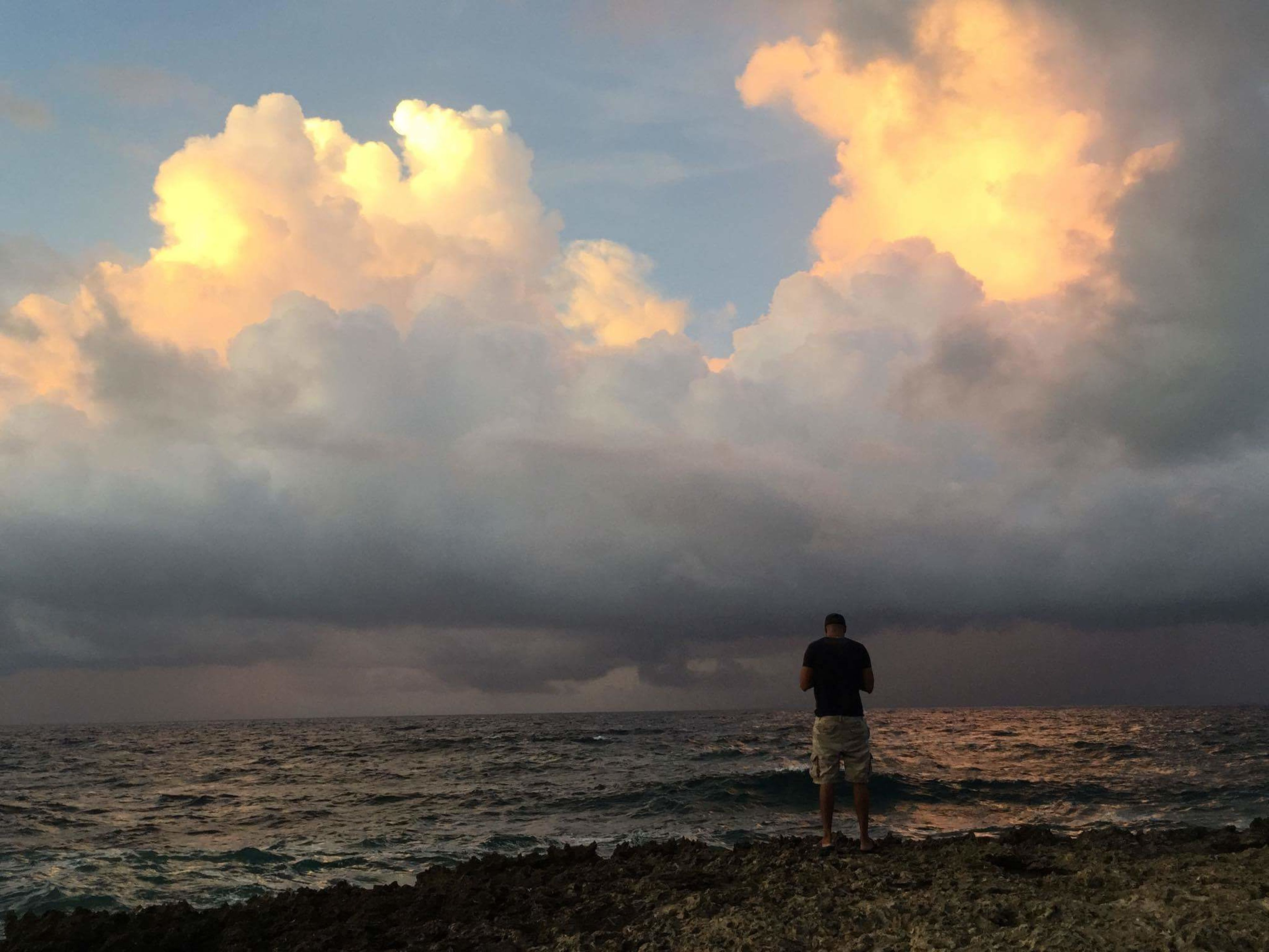 sea, horizon over water, tranquil scene, water, tranquility, scenics, silhouette, sky, standing, rear view, beauty in nature, men, idyllic, cloud - sky, nature, majestic, getting away from it all, escapism, solitude, remote, seascape, dramatic sky, calm, cloud, non-urban scene, shore, ocean, outdoors