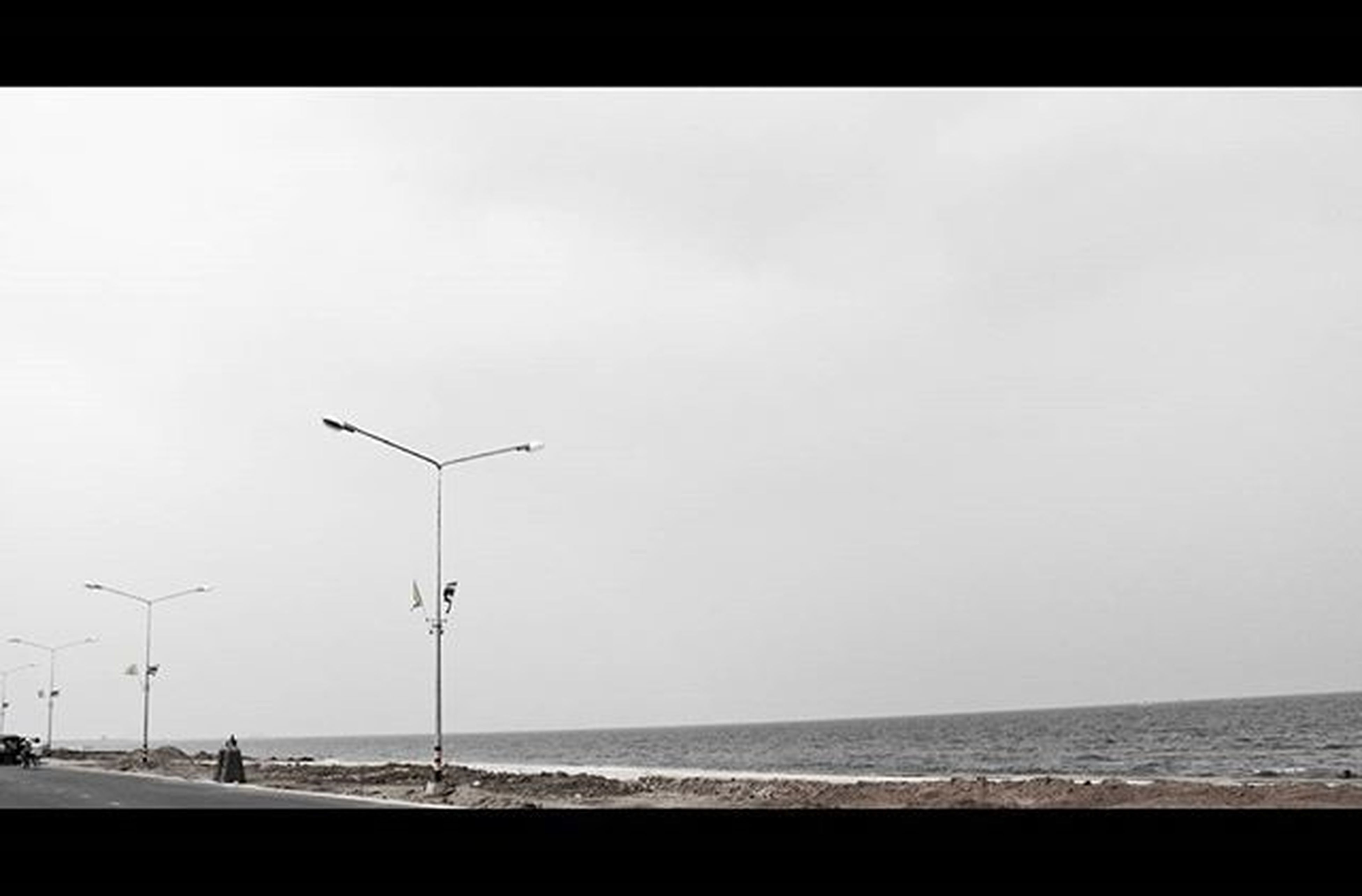 sea, horizon over water, beach, water, clear sky, copy space, shore, tranquility, tranquil scene, scenics, sand, beauty in nature, nature, street light, idyllic, sky, outdoors, incidental people, coastline, remote