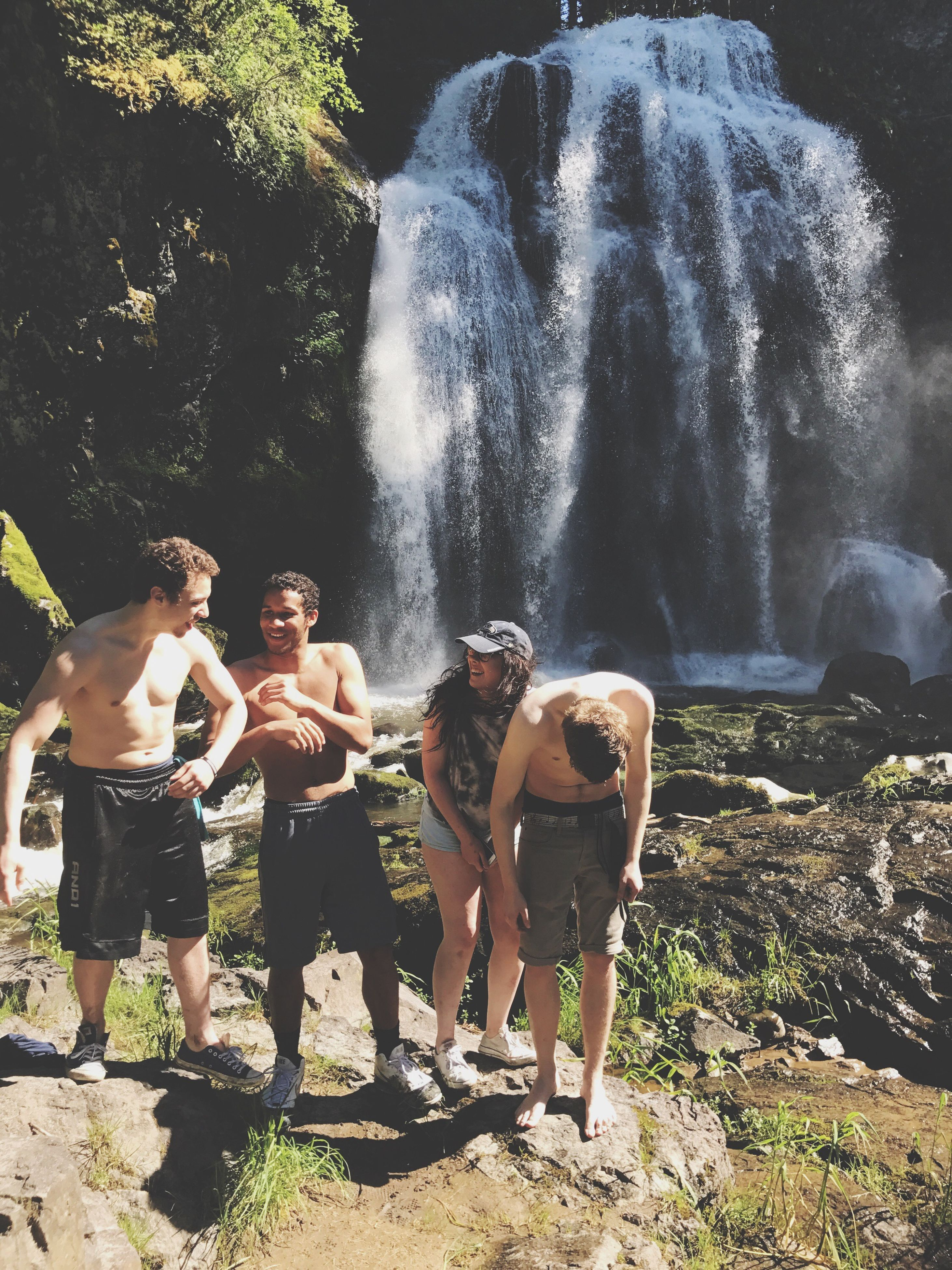 waterfall, motion, standing, water, long exposure, shirtless, rock - object, leisure activity, outdoors, nature, adventure, togetherness, vacations, real people, full length, fun, men, day, beauty in nature, lifestyles, tree, happiness, young adult, forest, friendship, boys, young women, spraying, hot spring, sky, people