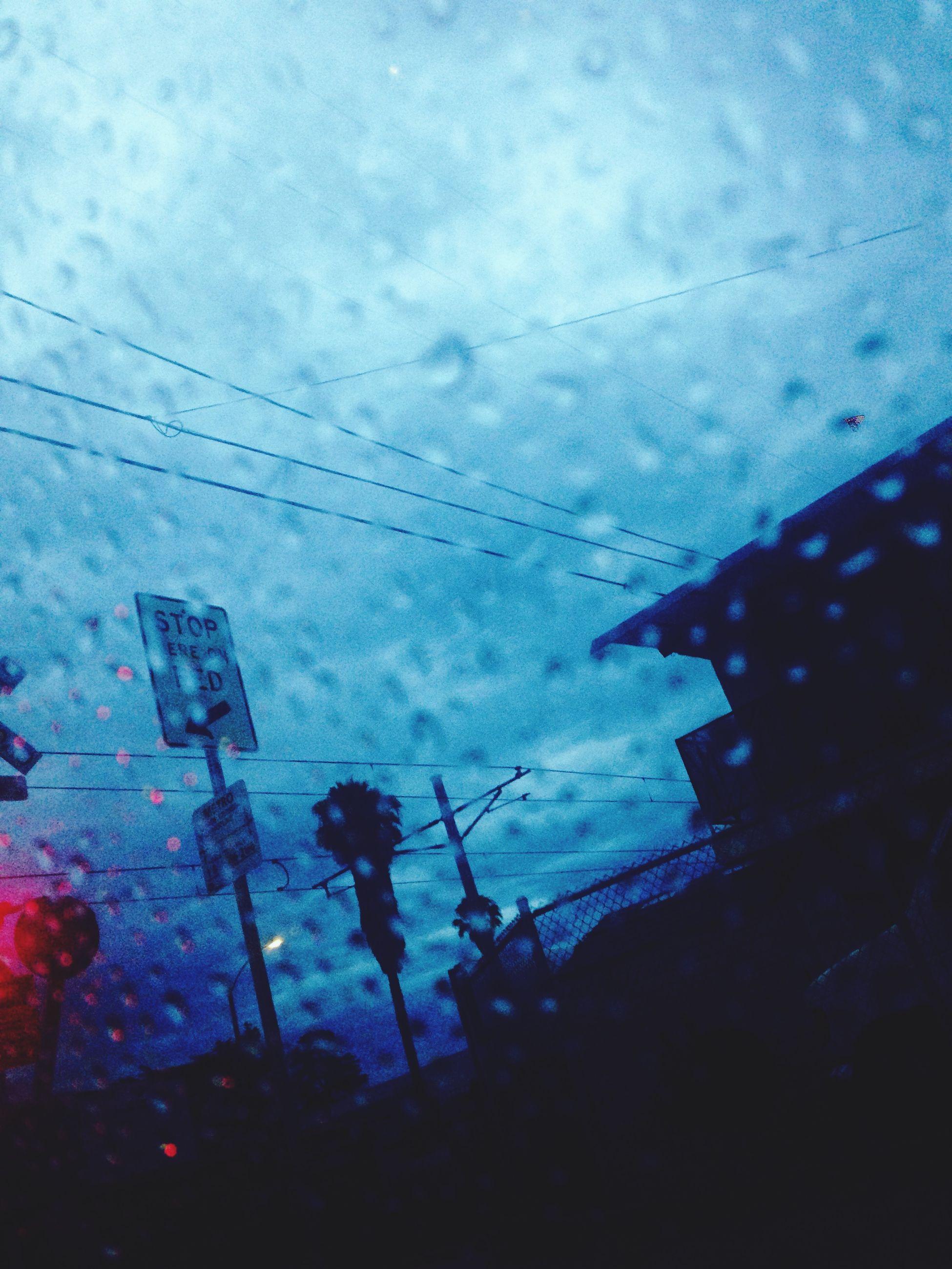 weather, sky, season, rain, wet, silhouette, building exterior, street, window, dusk, built structure, architecture, cloud - sky, car, glass - material, transparent, road, transportation, drop, power line