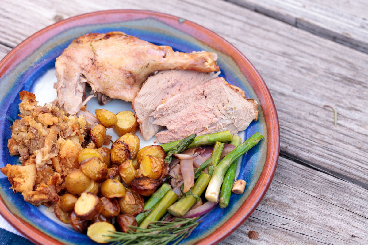 Rosemary roasted duck stuffed with bread stuffing and ringed with asparagus in a pottery dish during the holiday season. Asparagus Bird Dinner Duck Farm To Table Food Meat No People Plate Poultry Roasted Potatoes Rosemary Roasted Rustic Table Setting Thanksgiving