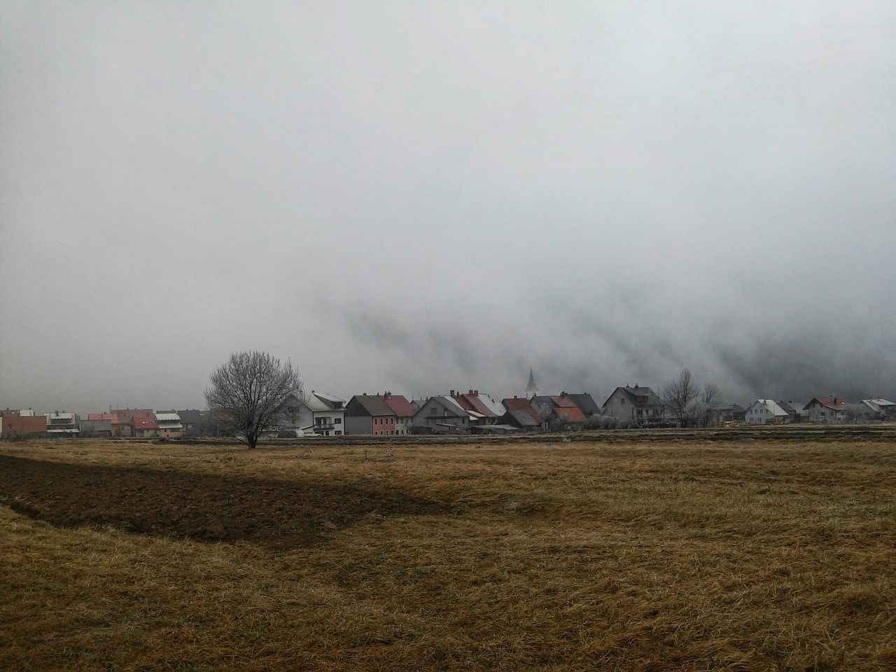 Houses On Field Against Sky During Foggy Weather